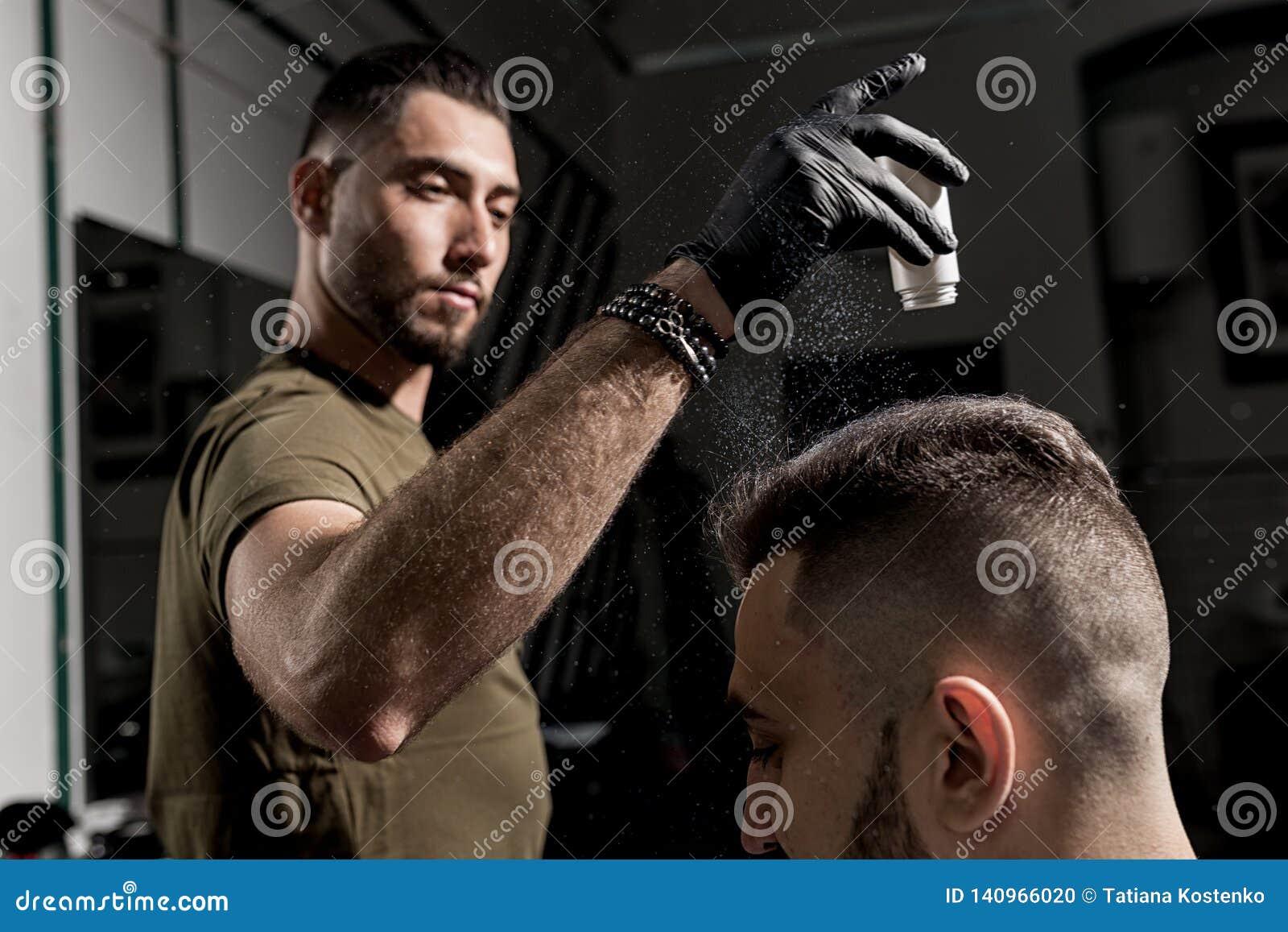 Ο όμορφος κουρέας καθορίζει τον προσδιορισμό του βάναυσου νέου γενειοφόρου ατόμου με ένα ξηρό styler σε ένα barbershop