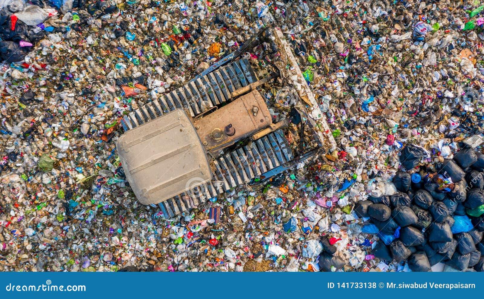 Ο σωρός απορριμάτων στην απόρριψη ή τα υλικά οδόστρωσης απορριμμάτων, εναέρια φορτηγά απορριμάτων άποψης ξεφορτώνει τα απορρίματα