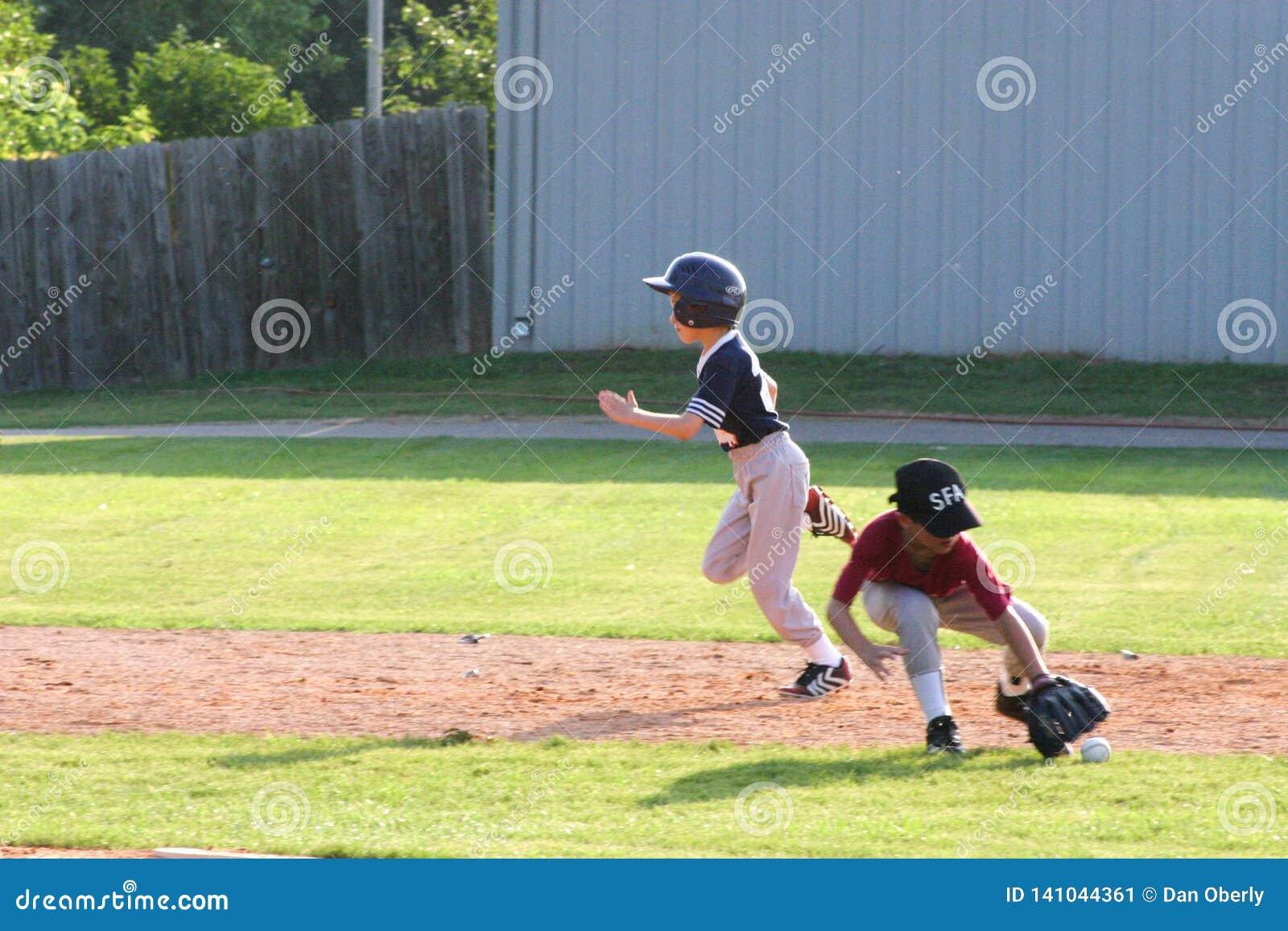 Ο φορέας σόφτμπολ μικρού πρωταθλήματος ορμά για το παίχτη τρίτης βάσης ενώ ο παίχτης δεύτερης βάσης φθάνει για τη σφαίρα