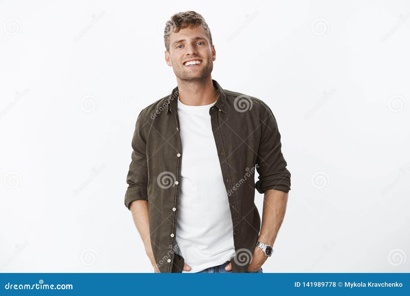Ο χαλαρωμένος, φιλικός όμορφος ευρωπαϊκός τύπος με τη σκληρή τρίχα που χαμογελά χαρωπά με το άσπρο υγιές κράτημα δοντιών παραδίδε