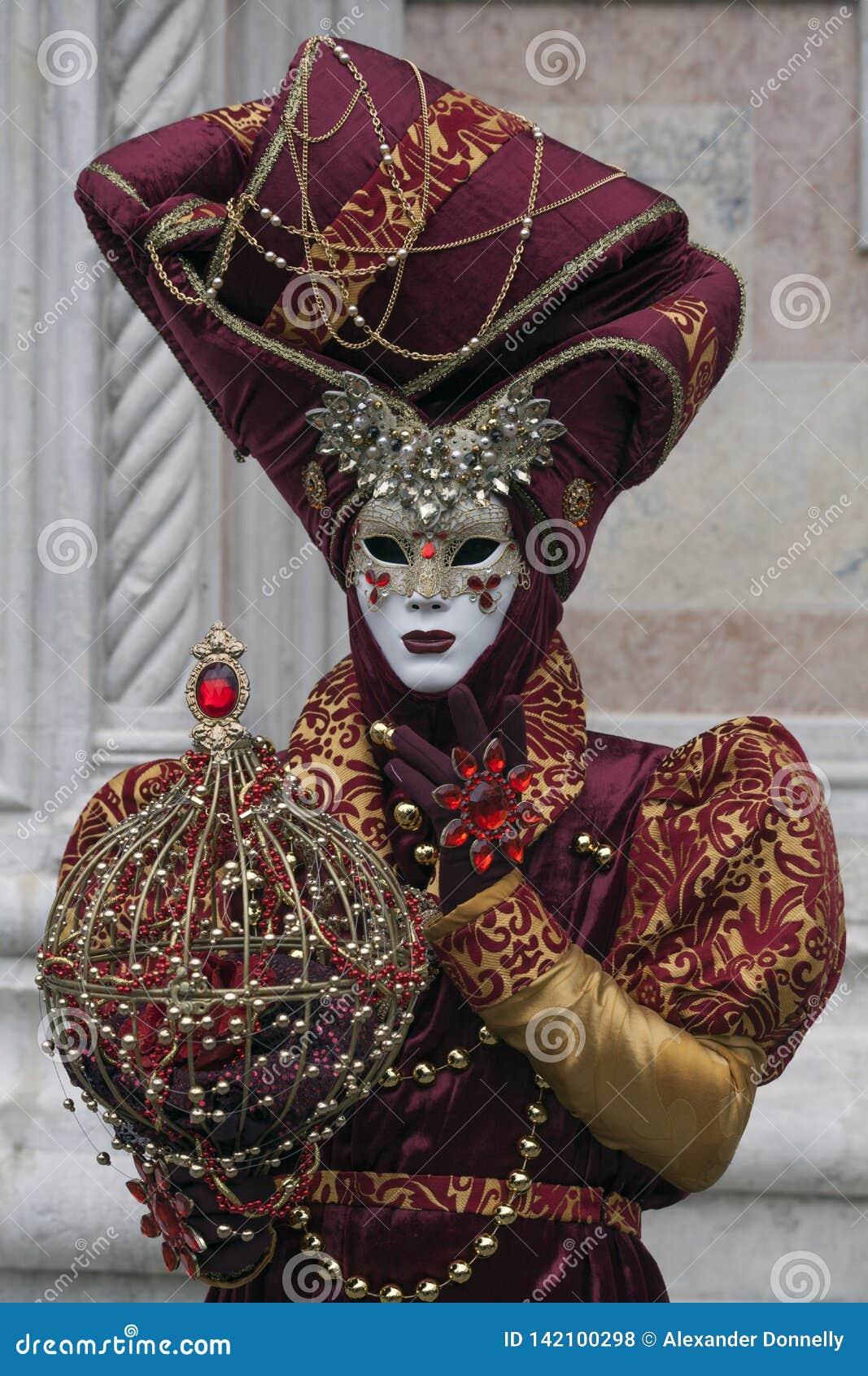 Ο χαρακτήρας της Βενετίας καρναβάλι έντυσε σε ένα ζωηρόχρωμες κόκκινες και χρυσές κοστούμι και μια μάσκα το Φεβρουάριο Βενετία Ιτ