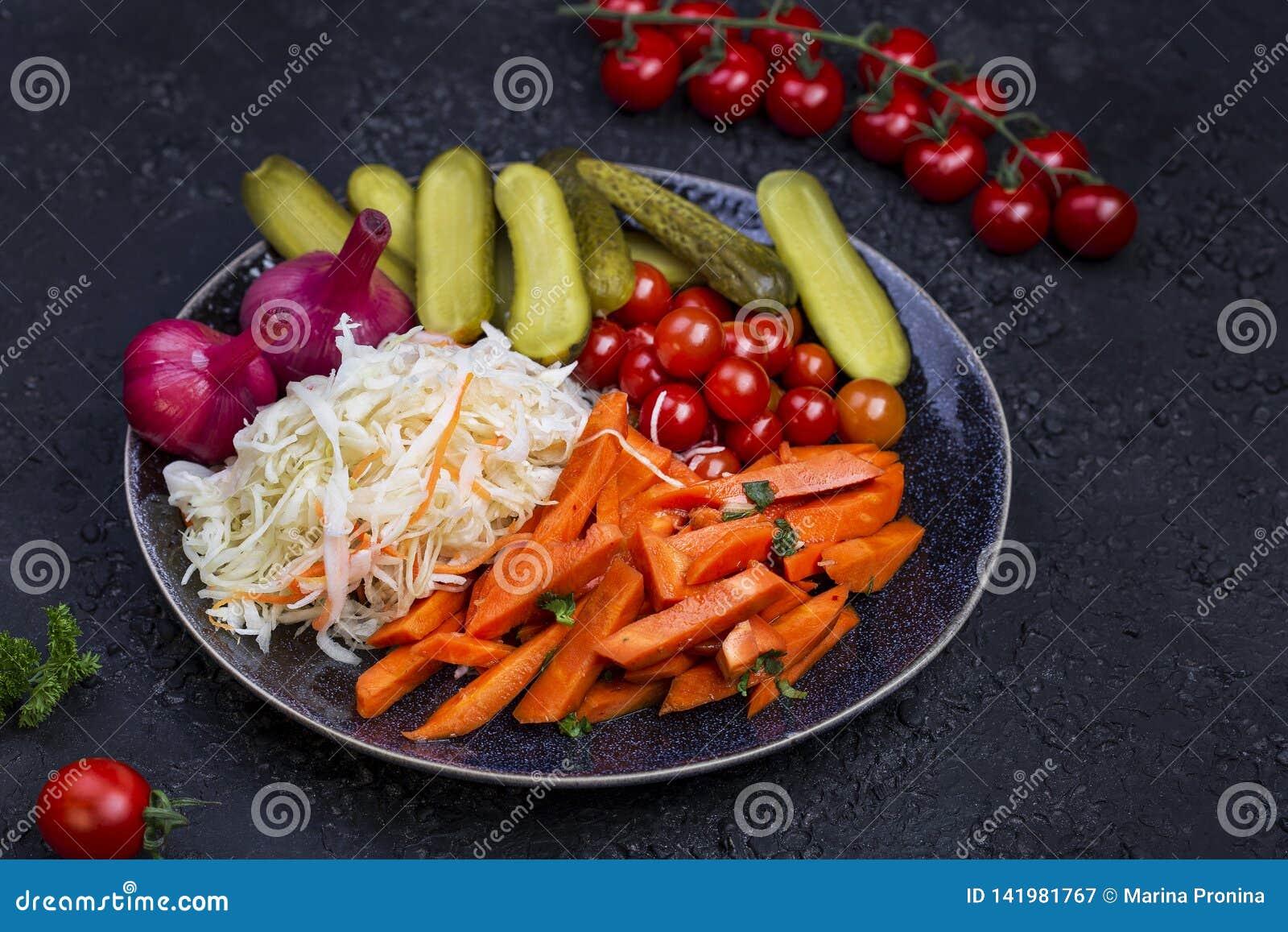 Διαφορετικοί τύποι παστωμένων λαχανικών σε ένα σκοτεινό υπόβαθρο