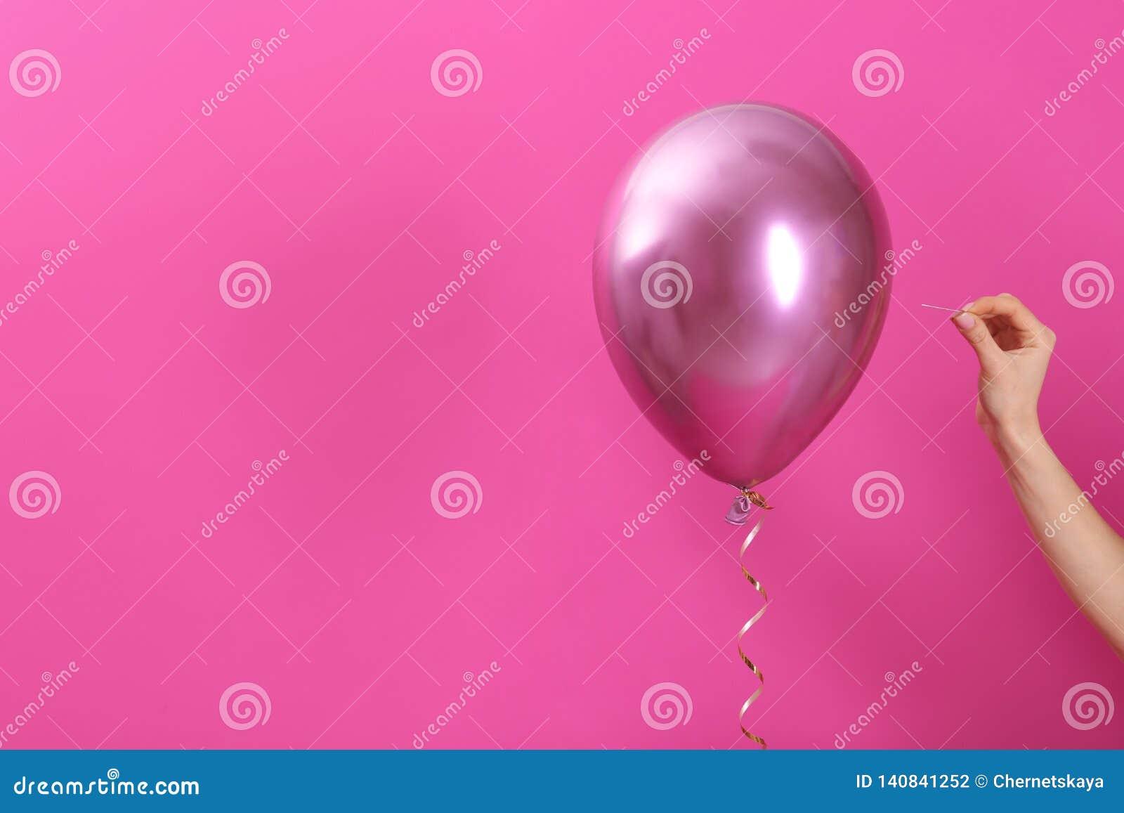 Διαπεραστικό μπαλόνι γυναικών με τη βελόνα στο υπόβαθρο χρώματος, κινηματογράφηση σε πρώτο πλάνο