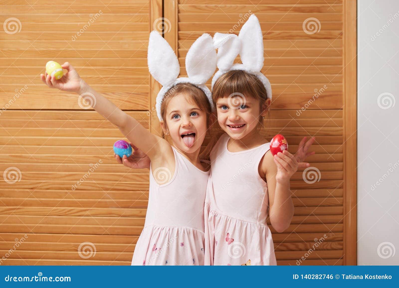 Δύο αστείες γοητευτικές μικρές αδελφές στα φορέματα με τα αυτιά του άσπρου κουνελιού στα κεφάλια τους κρατούν τα βαμμένα αυγά στα