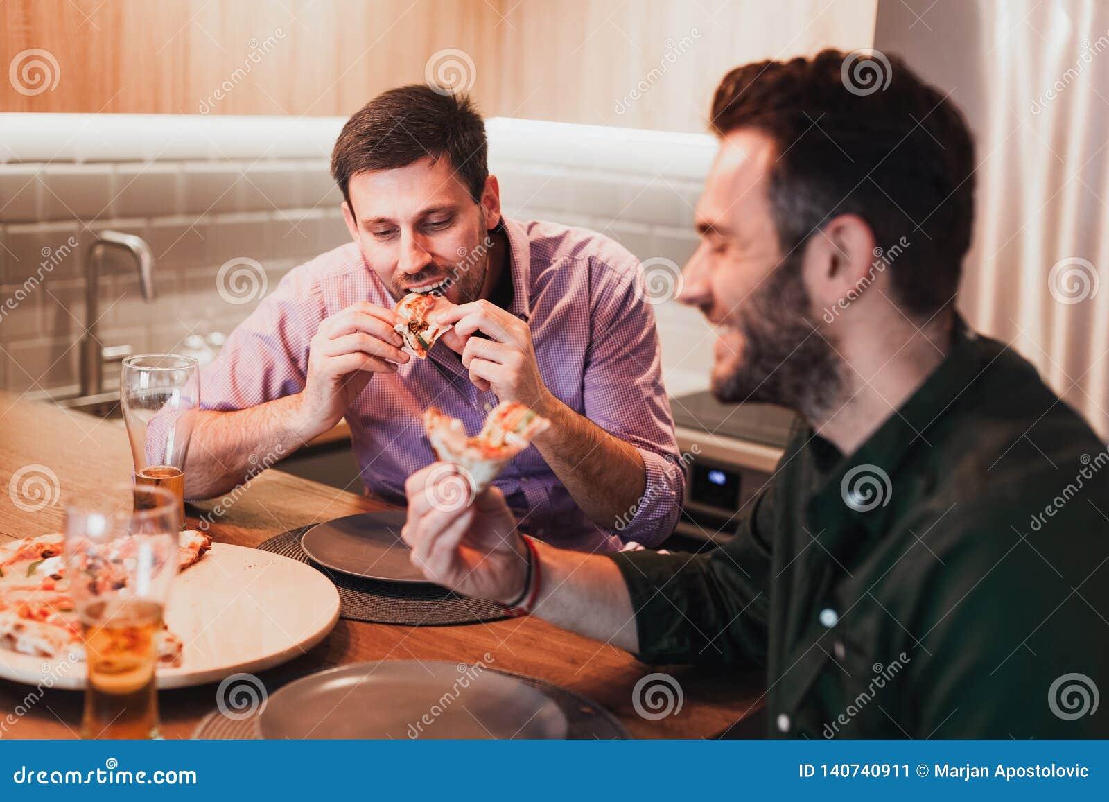 Δύο τύποι που τρώνε την πίτσα στο σπίτι