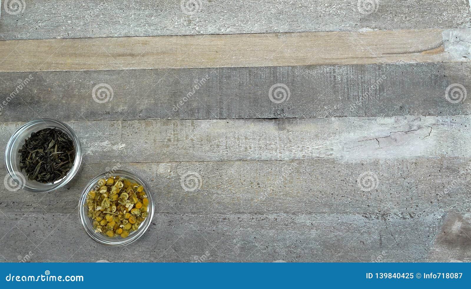 Δύο φλυτζάνια τσαγιού στο γυαλί με το μαύρο τσάι και το chamomile τσάι στο φυσικό ξύλινο υπόβαθρο