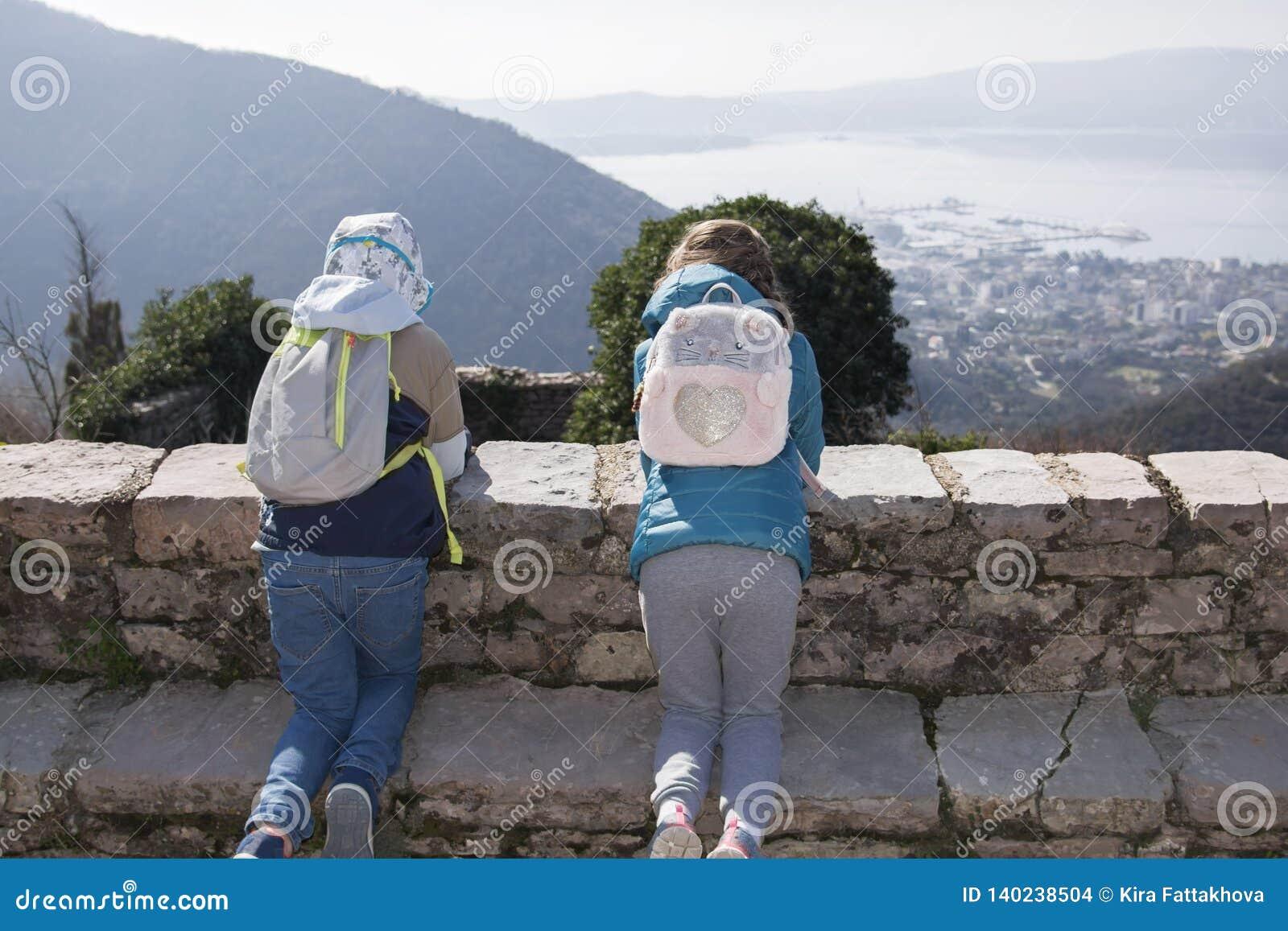 Δύο παιδιά γονατίζουν σε έναν τοίχο πετρών σε ένα ορεινό χωριό την πρώιμη άνοιξη και εξετάζουν κάτω τον κόλπο και την πόλη, Gornj