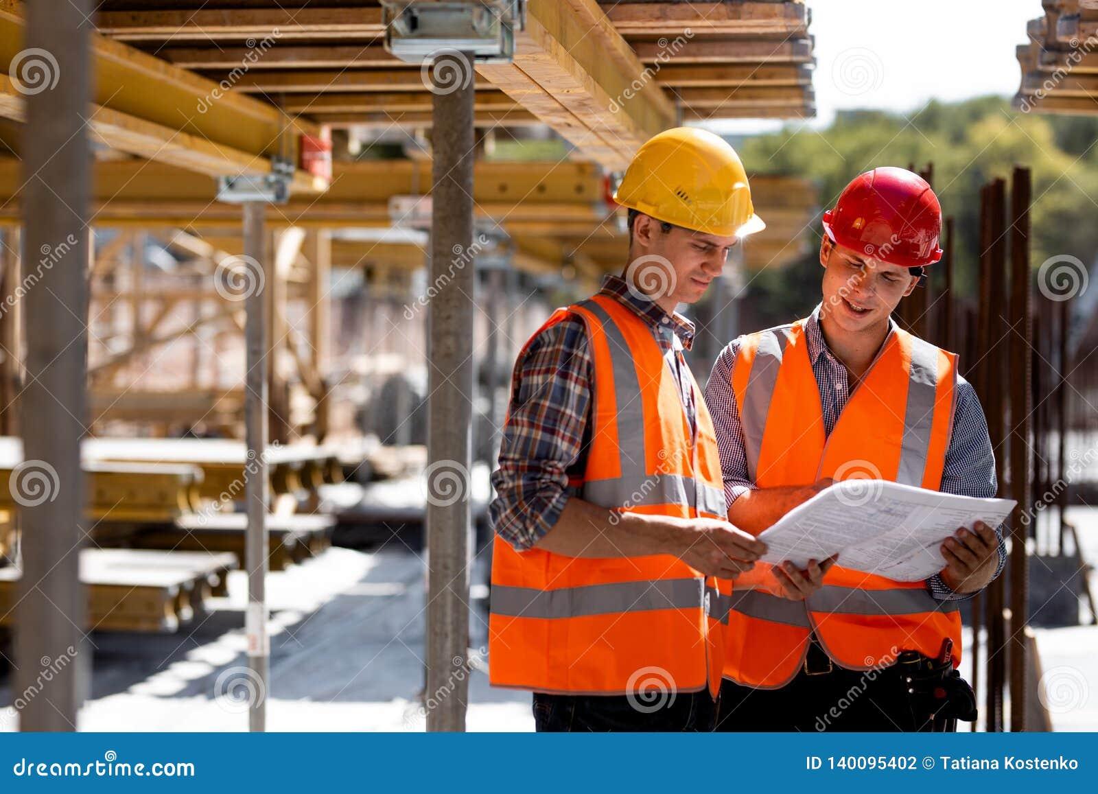 Δύο πολιτικοί μηχανικοί που ντύνονται στις πορτοκαλιά φανέλλες και τα κράνη εργασίας εξερευνούν την τεκμηρίωση κατασκευής στο εργ
