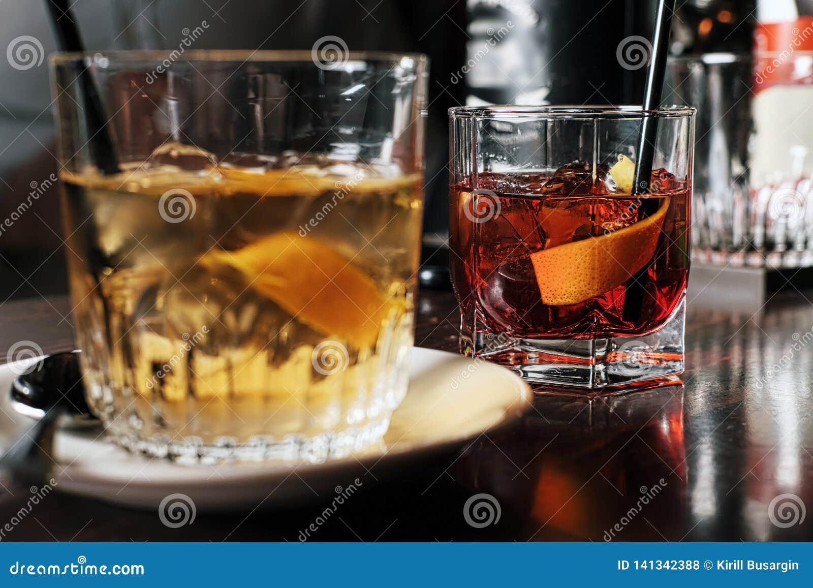 Δύο ποτήρια του κοκτέιλ με την πορτοκαλιά φέτα εικόνα που τονίζεται