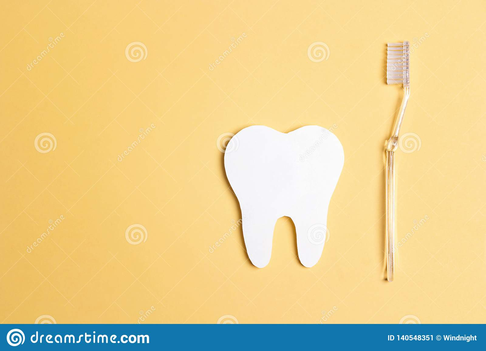Δόντι της Λευκής Βίβλου με την οδοντόβουρτσα στο κίτρινο υπόβαθρο Έννοια οδοντικής υγείας Έννοια ημέρας οδοντιάτρων