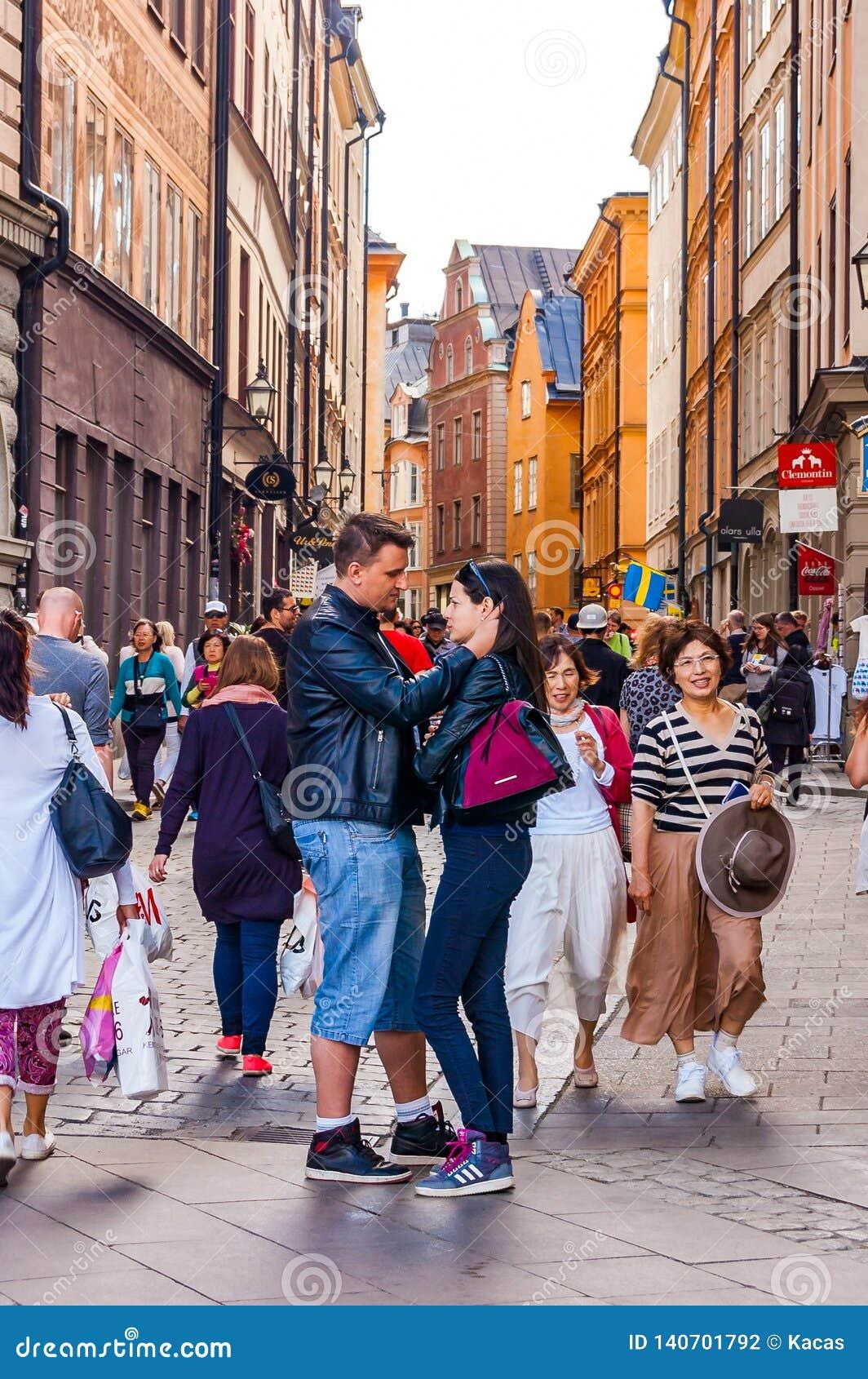 Ρομαντικό ζεύγος που στέκεται στο κέντρο της συσσωρευμένης μεσαιωνικής οδού σε Gamla Stan, παλαιά πόλη της Στοκχόλμης