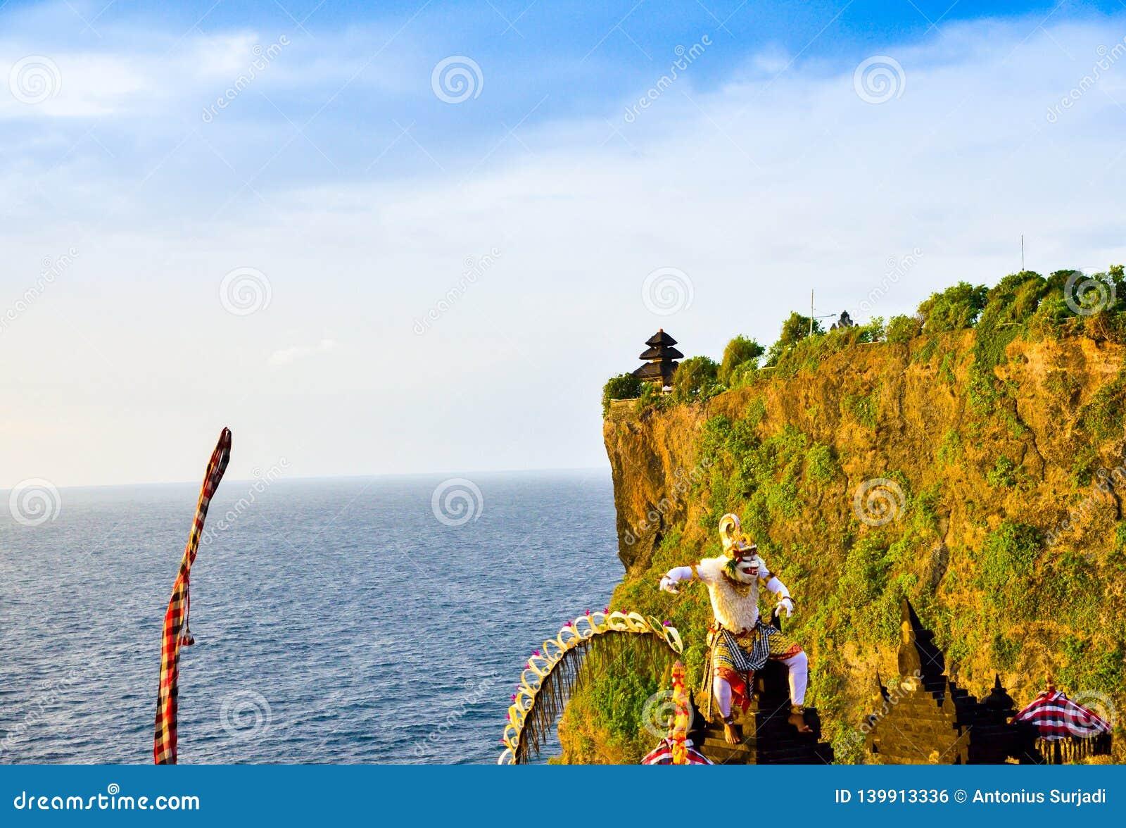 Ρομαντικό ηλιοβασίλεμα Goregeous στον απότομο βράχο πάνω από το βουνό με τον ιερό ναό στο τοπ και λευκό χαρακτήρα Θεών πιθήκων