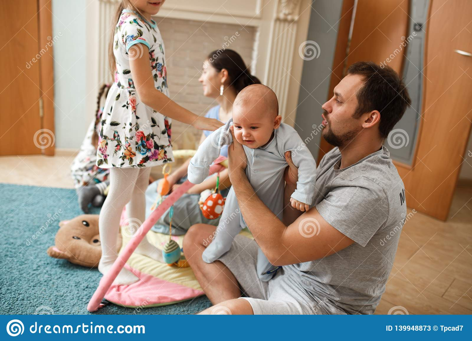 Όλος ο οικογενειακός πατέρας, μητέρα, δύο κόρες και λίγος χρόνος εξόδων γιων μωρών στον τάπητα στο δωμάτιο