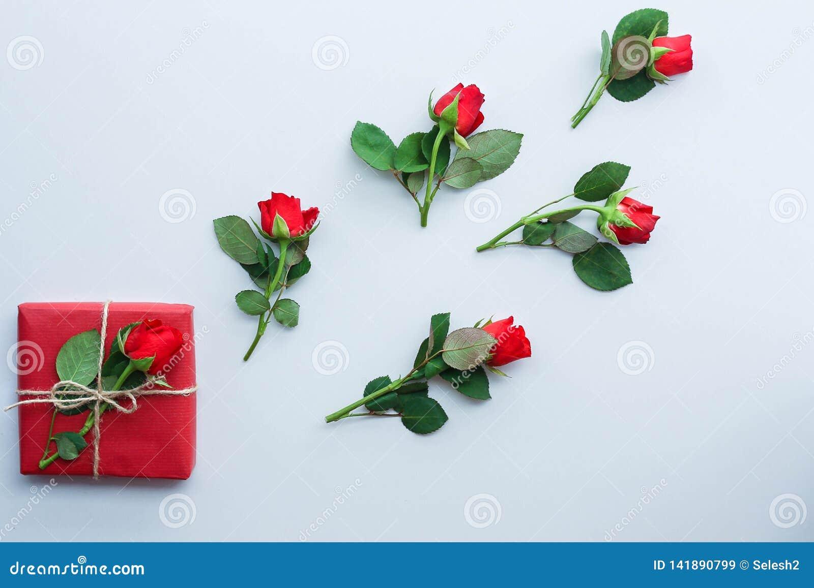 Όμορφα τριαντάφυλλα και κιβώτιο δώρων στο ελαφρύ υπόβαθρο