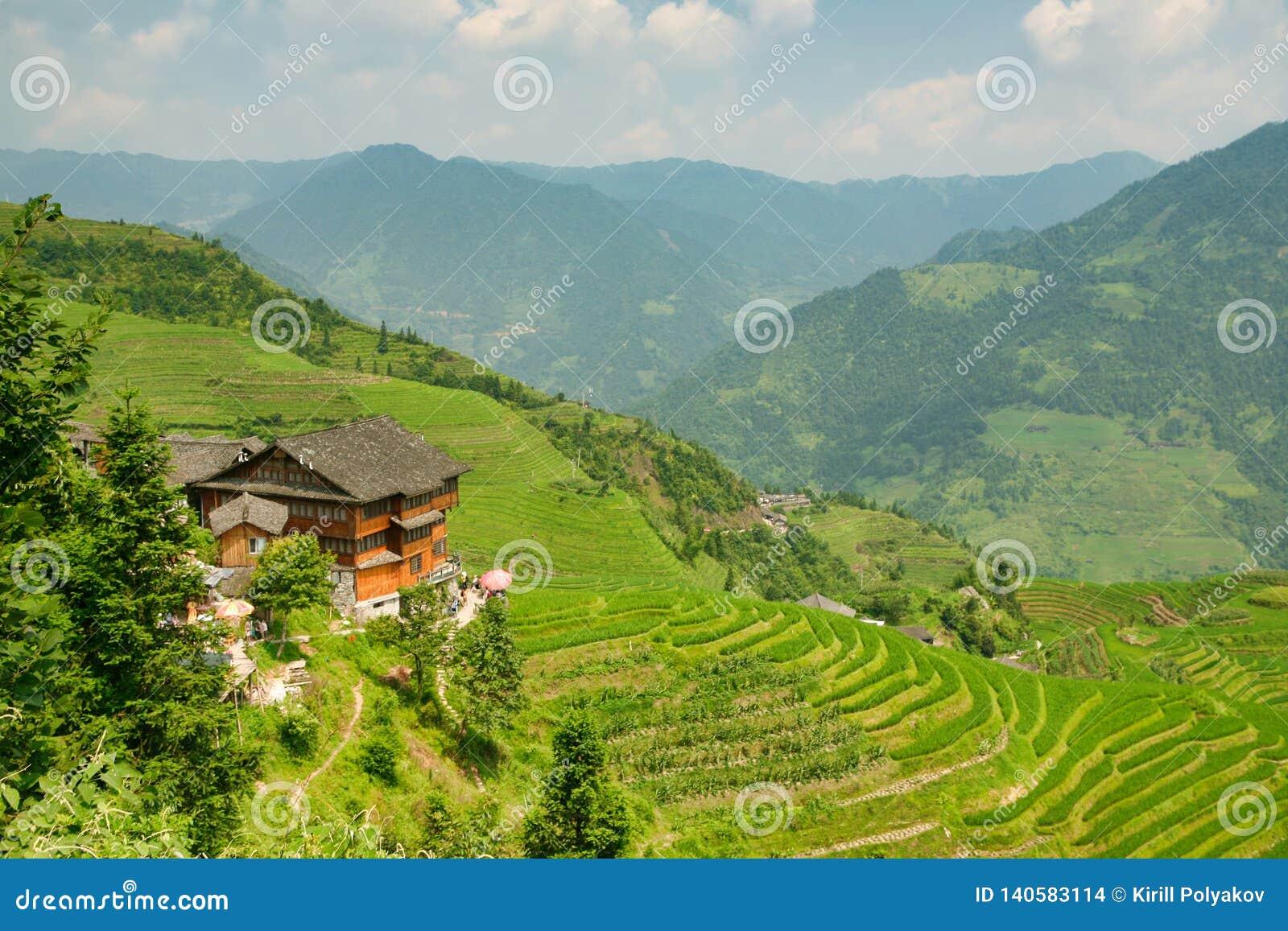 Όμορφη άποψη των σπιτιών του χωριού Dazhay, των πεζουλιών ρυζιού και των βουνών