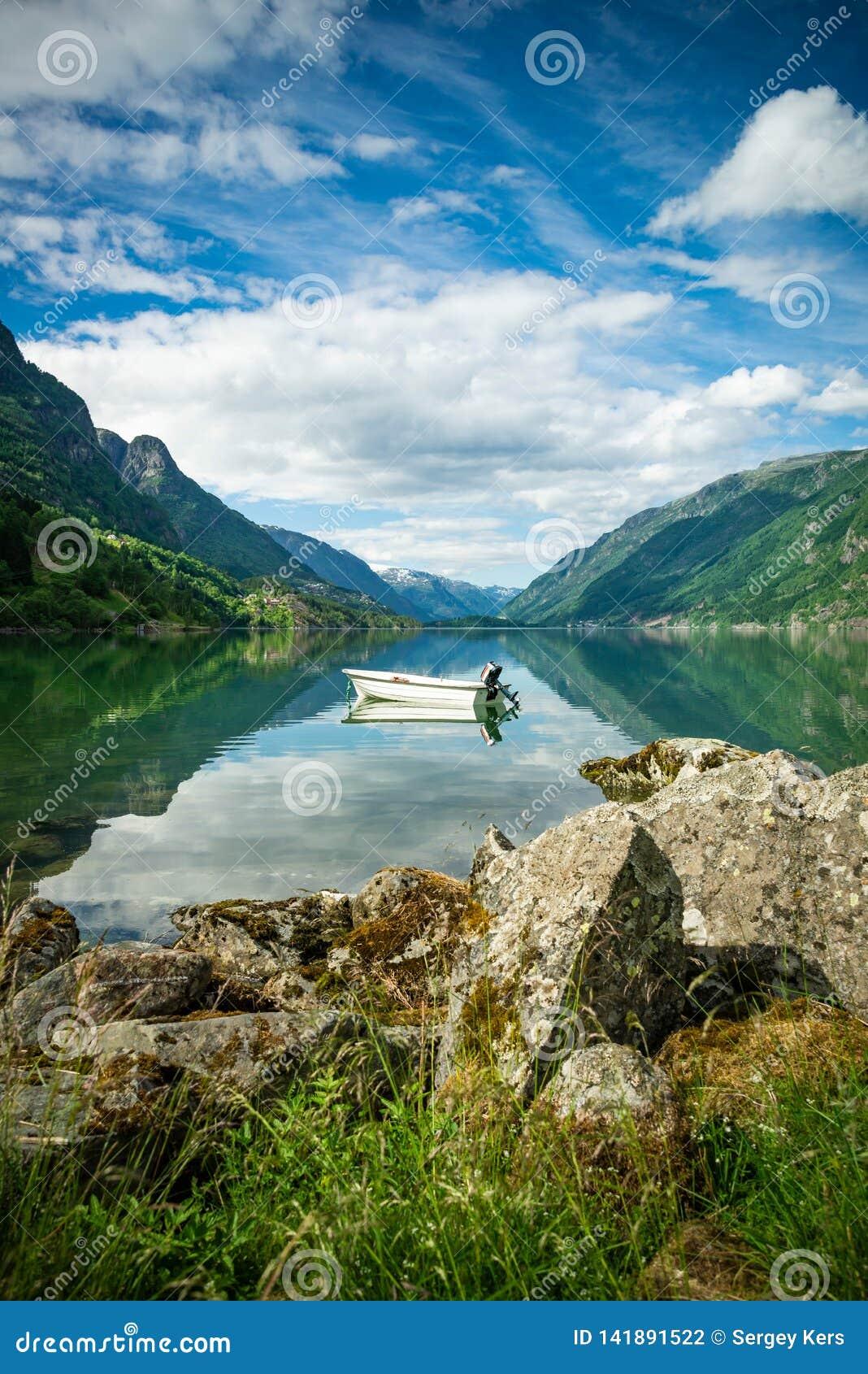 Όμορφη άποψη των φιορδ της Νορβηγίας με μια βάρκα στα ήρεμα νερά