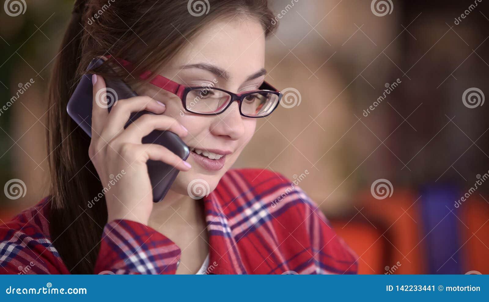 Όμορφη γυναίκα eyeglasses που μιλούν στο smartphone, την επικοινωνία και τη συσκευή