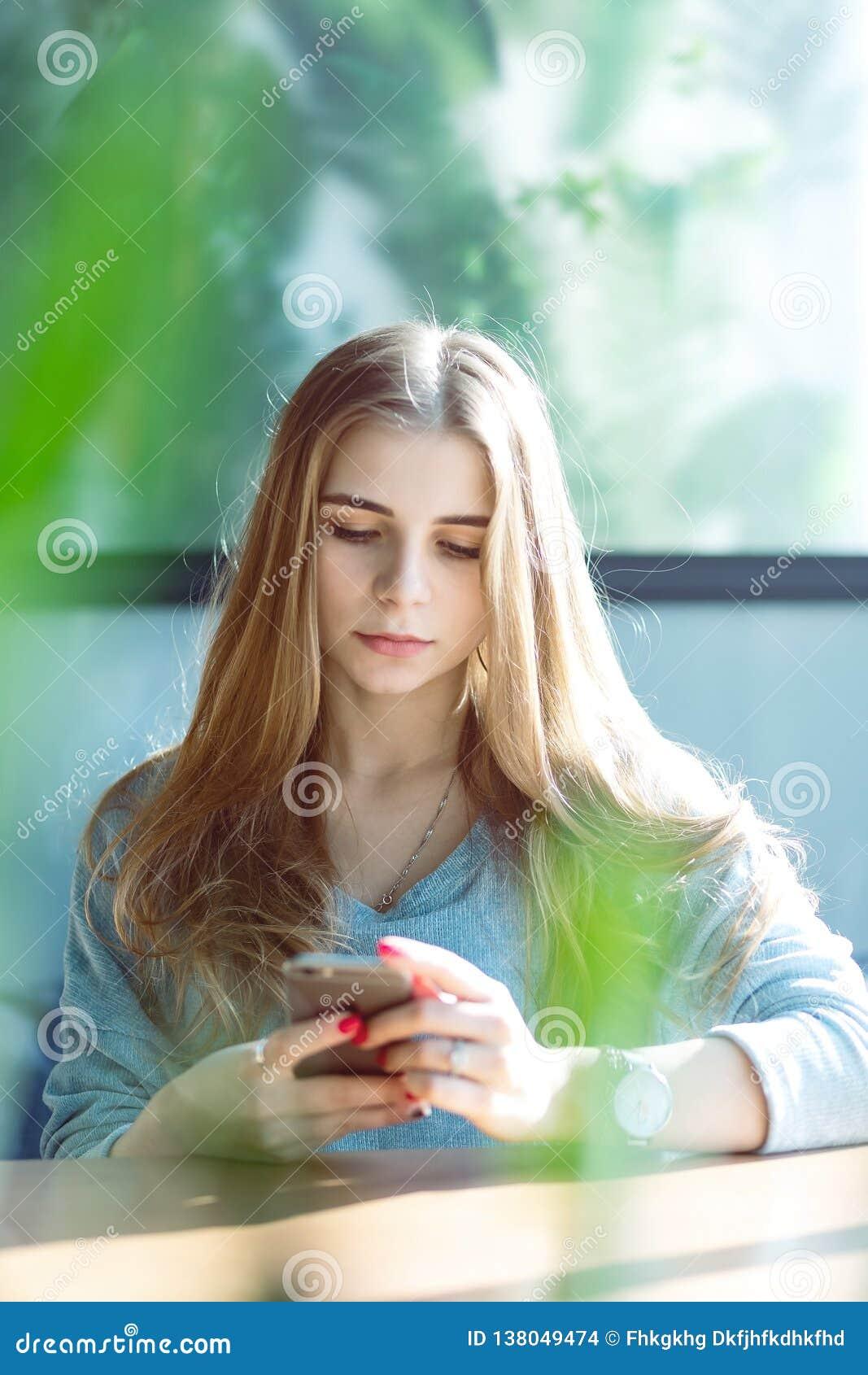 Όμορφη νέα γυναίκα που βάζει σε έναν καναπέ στο σπίτι, χρησιμοποιώντας το κινητό τηλέφωνο