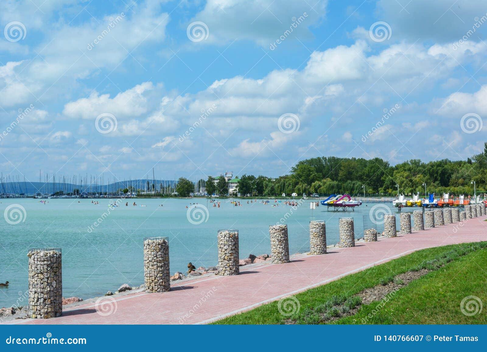Όμορφη παραλία με τις πλέοντας βάρκες και τις βάρκες κουπιών στη λίμνη Balaton