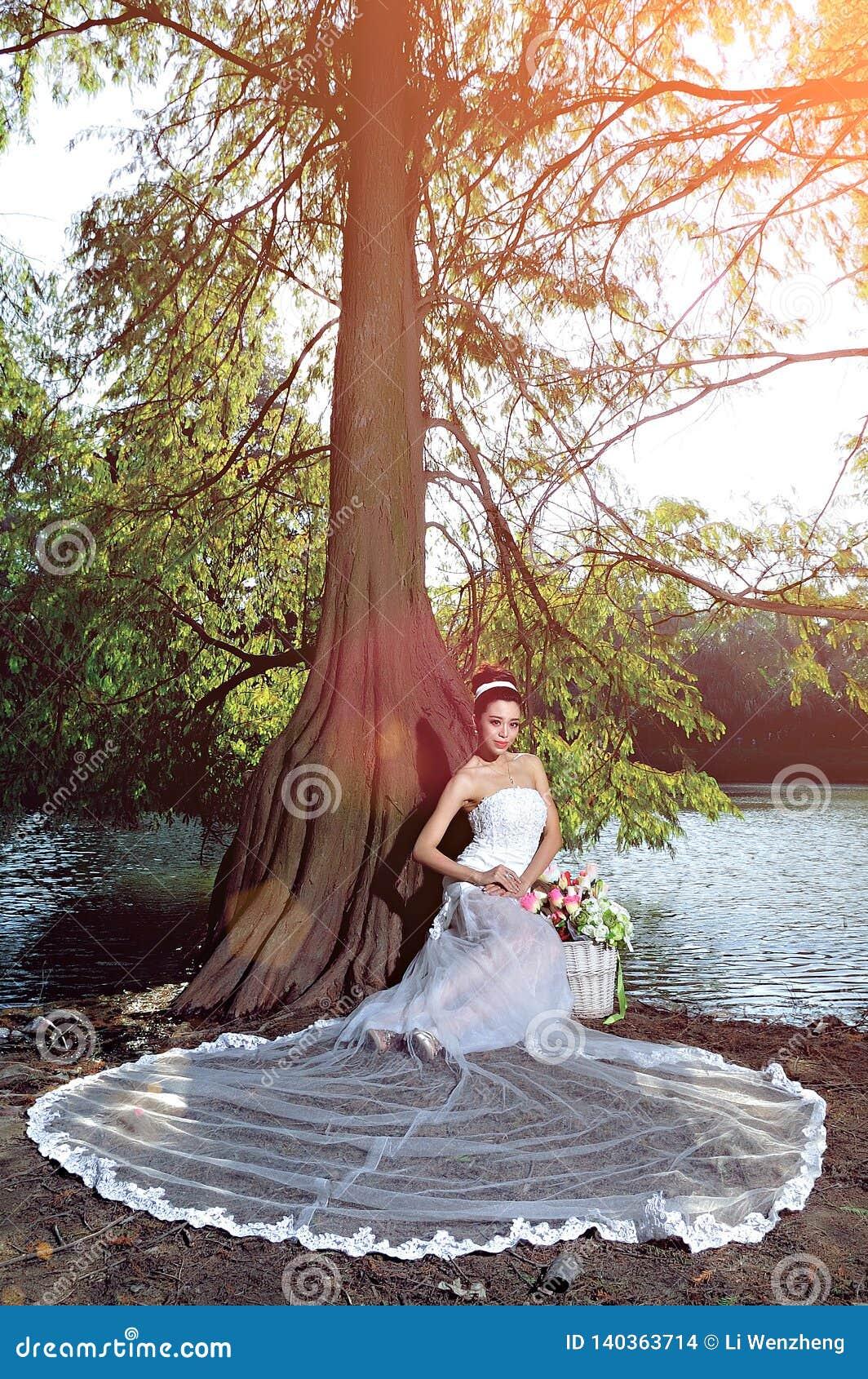 Όμορφο ασιατικό κορίτσι σε ένα γαμήλιο φόρεμα που παρουσιάζει ευτυχείς στιγμές