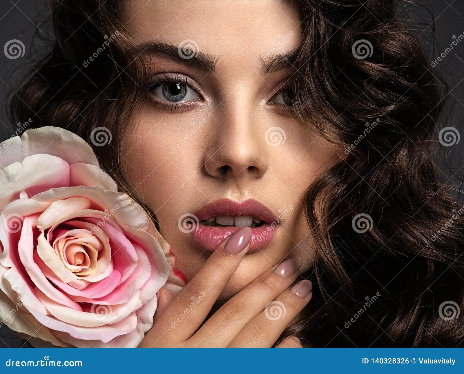 Όμορφο πρόσωπο μιας νέας γυναίκας με ένα καπνώές μάτι makeup