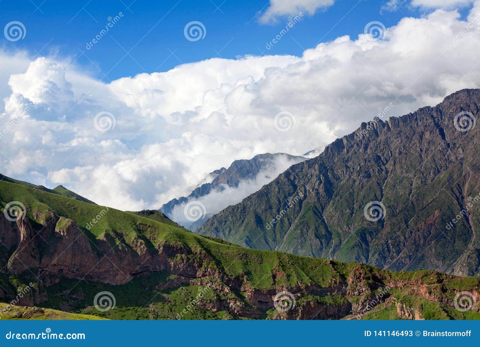 Σειρές και βουνά βουνών στο μπλε ουρανό και την άσπρη μεγάλη κινηματογράφηση σε πρώτο πλάνο υποβάθρου σύννεφων, καυκάσια βουνά, β