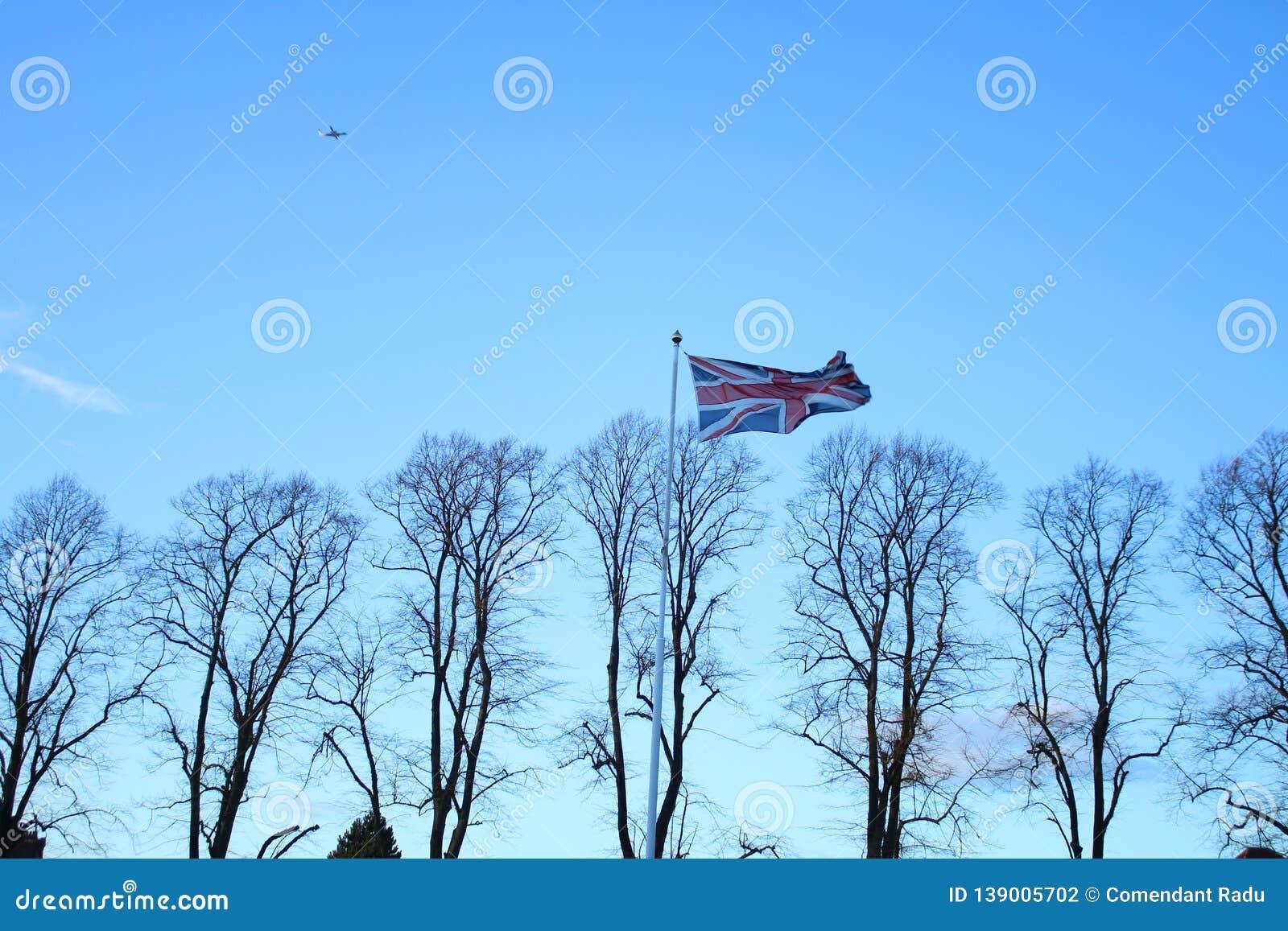 Σημαία της Μεγάλης Βρετανίας που κυματίζει στον αέρα Ταπετσαρία με το σαφή μπλε ουρανό