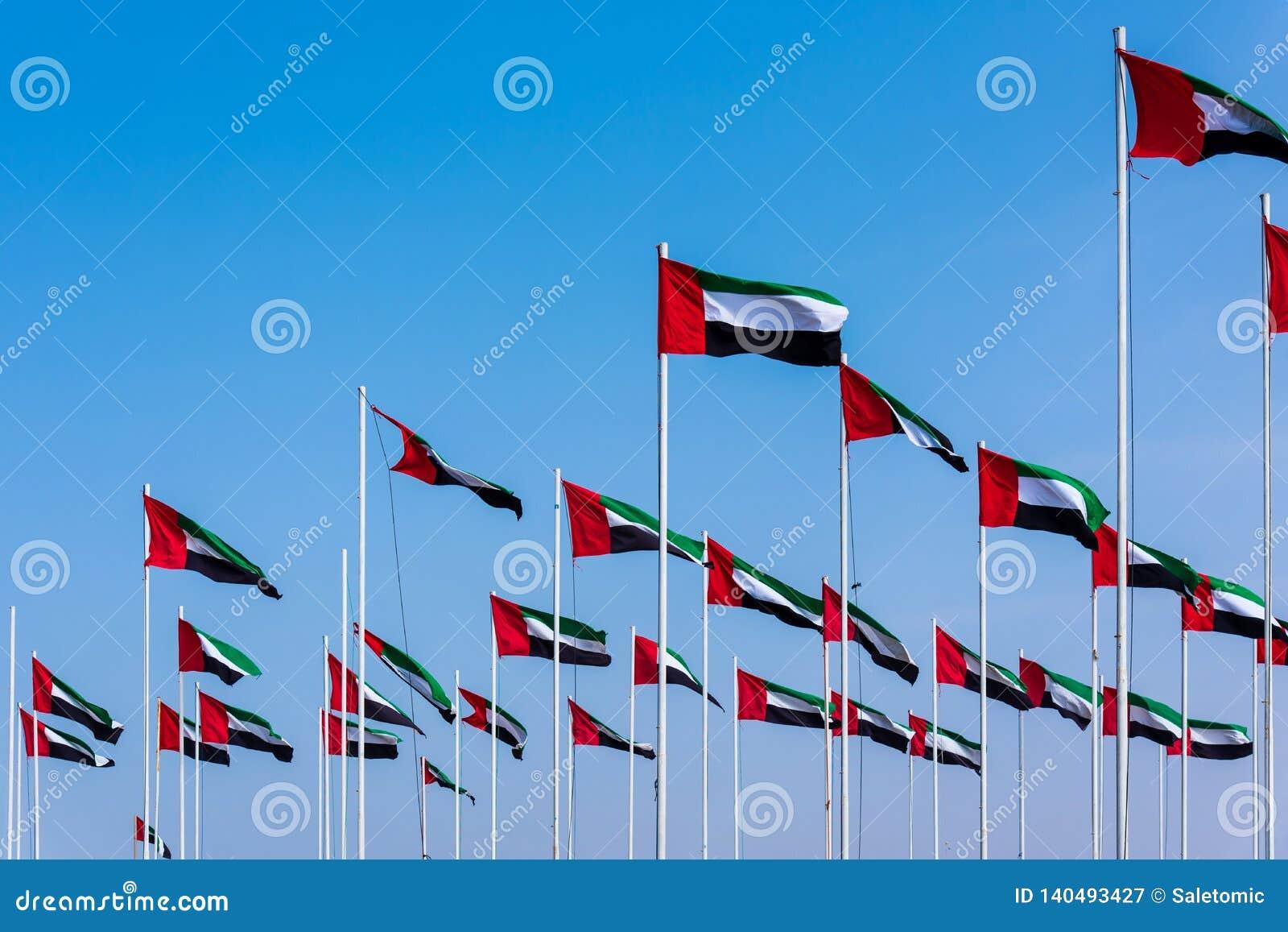 Σημαίες των Ηνωμένων Αραβικών Εμιράτων που τυλίγουν στον αέρα ενάντια στο μπλε ουρανό