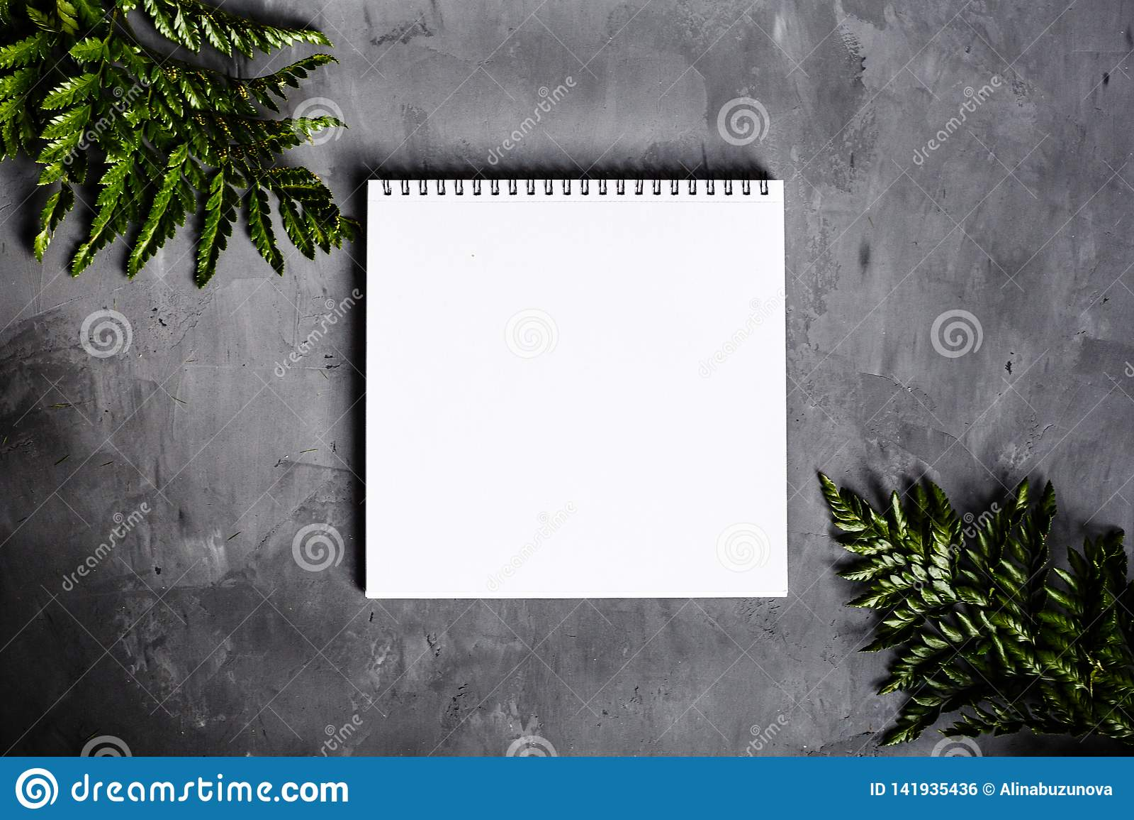 Σημειωματάριο και πράσινα φύλλα που βρίσκονται στο γκρίζο υπόβαθρο Επίπεδος βάλτε, τοπ άποψη τοποθετήστε το κείμενο