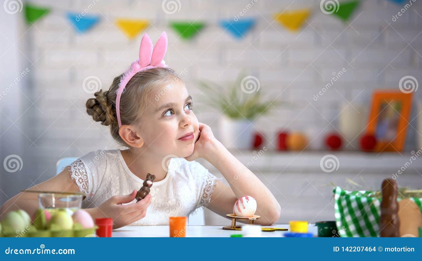 Σκεπτικό κορίτσι που ονειρεύεται για τον εορτασμό διακοπών Πάσχας, που κρατά το λαγουδάκι σοκολάτας