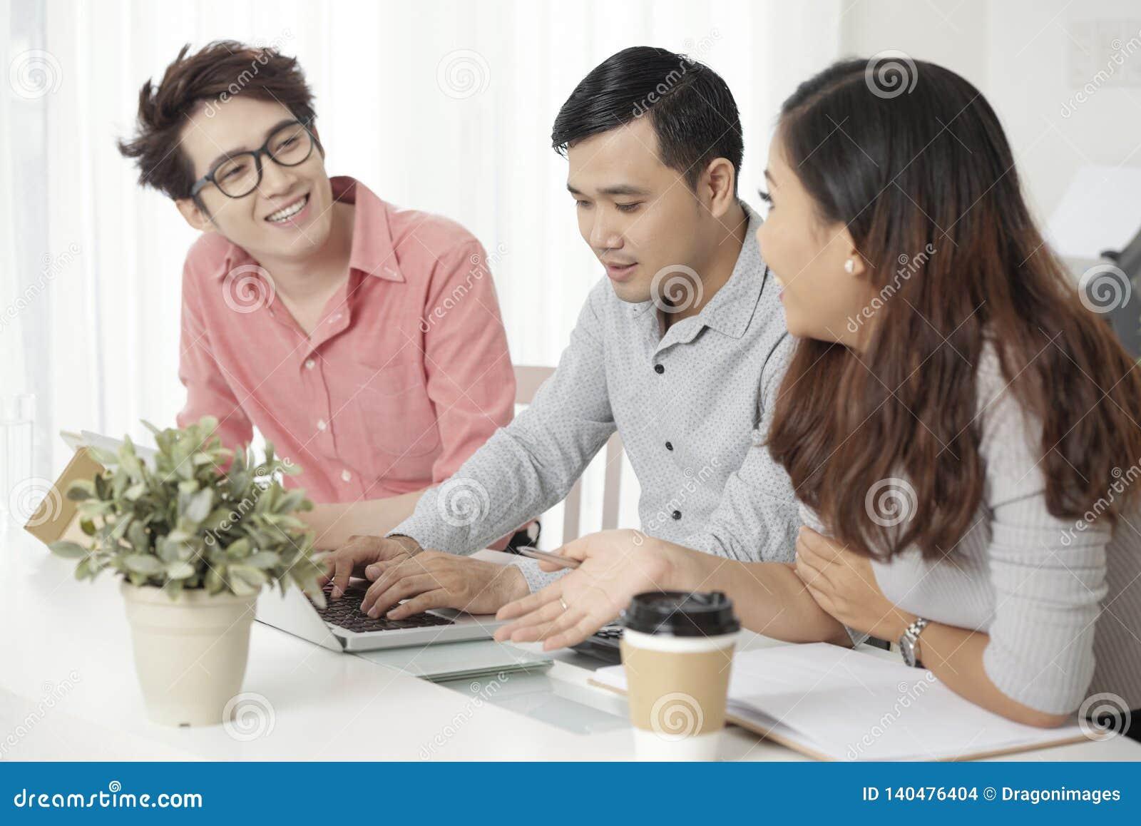 Σύγχρονοι ασιατικοί συνάδελφοι με το lap-top στο γραφείο