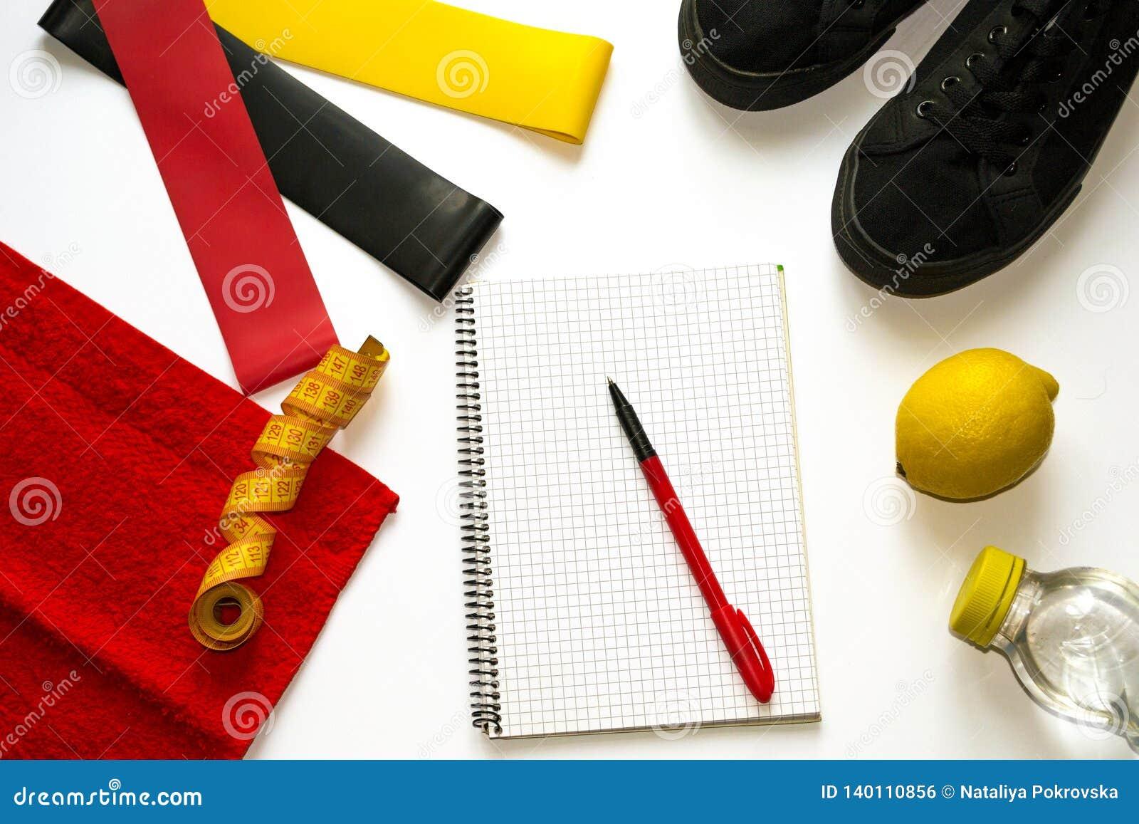 Σύνθεση ικανότητας γυναικών με τους ελαστικούς αποσυμπιεστές γόμμας, πάνινα παπούτσια, σημειωματάριο, παν, νωποί καρποί, λεμόνι,