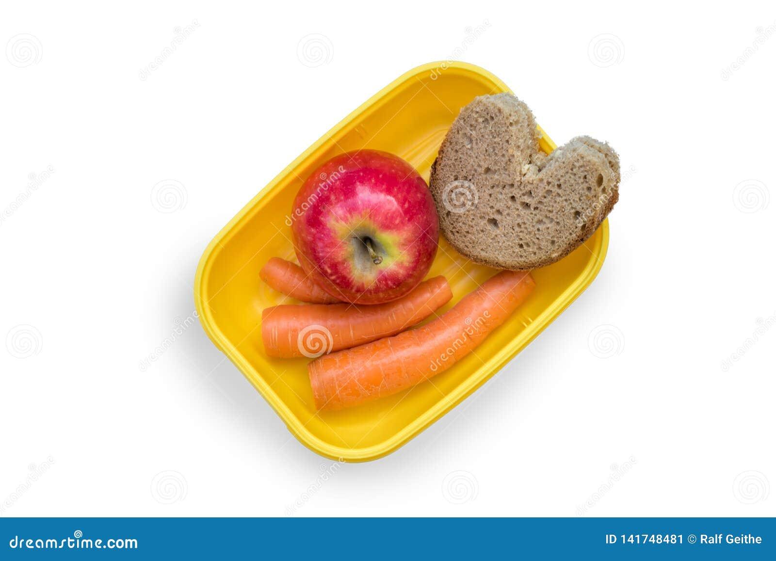 Στοργικά έτοιμο καλαθάκι με φαγητό με το ψωμί, το μήλο και τα καρότα μεσημεριανού γεύματος στο άσπρο υπόβαθρο