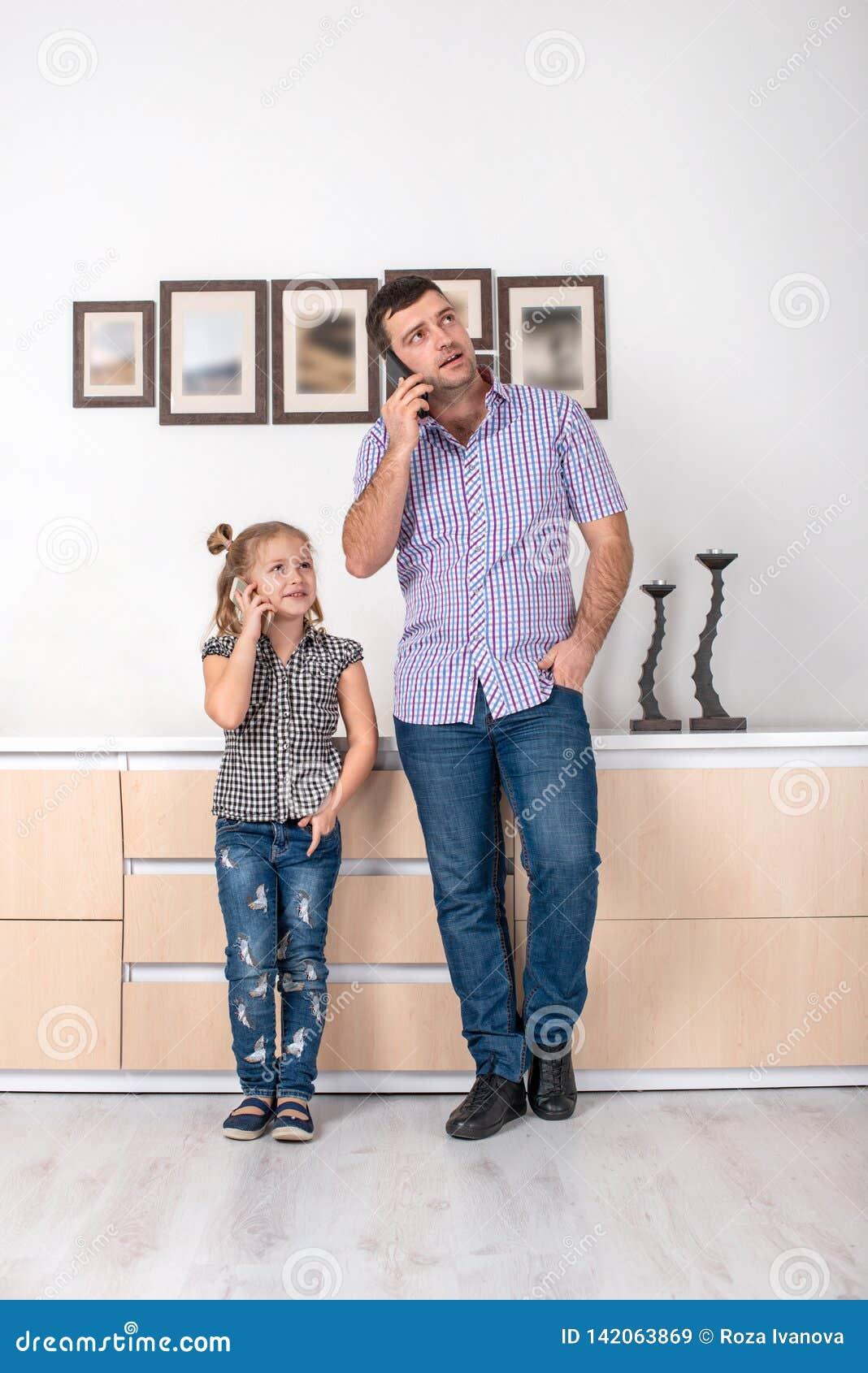 Στούντιο που πυροβολείται ενός μικρού κοριτσιού και του μπαμπά της που στέκονται στο σπίτι και που μιλούν στο τηλέφωνο τον ίδιο τ