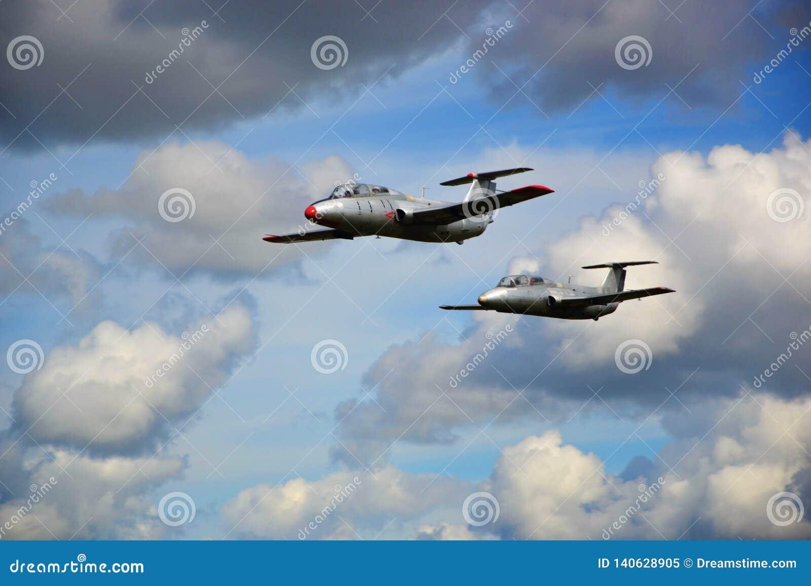 Στρατιωτικό αεροπλάνο δύο που πετά στα άσπρα σύννεφα