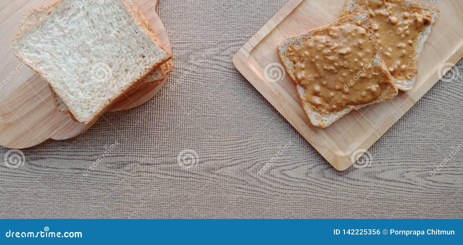 Σωρός ολόκληρου του ψωμιού σίτου και κάποιου φυστικοβουτύρου στην κορυφή