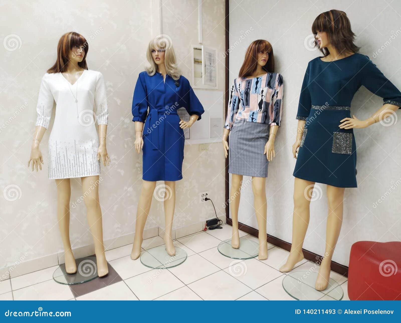 Τέσσερα θηλυκά μανεκέν έντυσαν στη διάφορη θηλυκή στάση ενδυμάτων στη γωνία στο κατάστημα Ostin