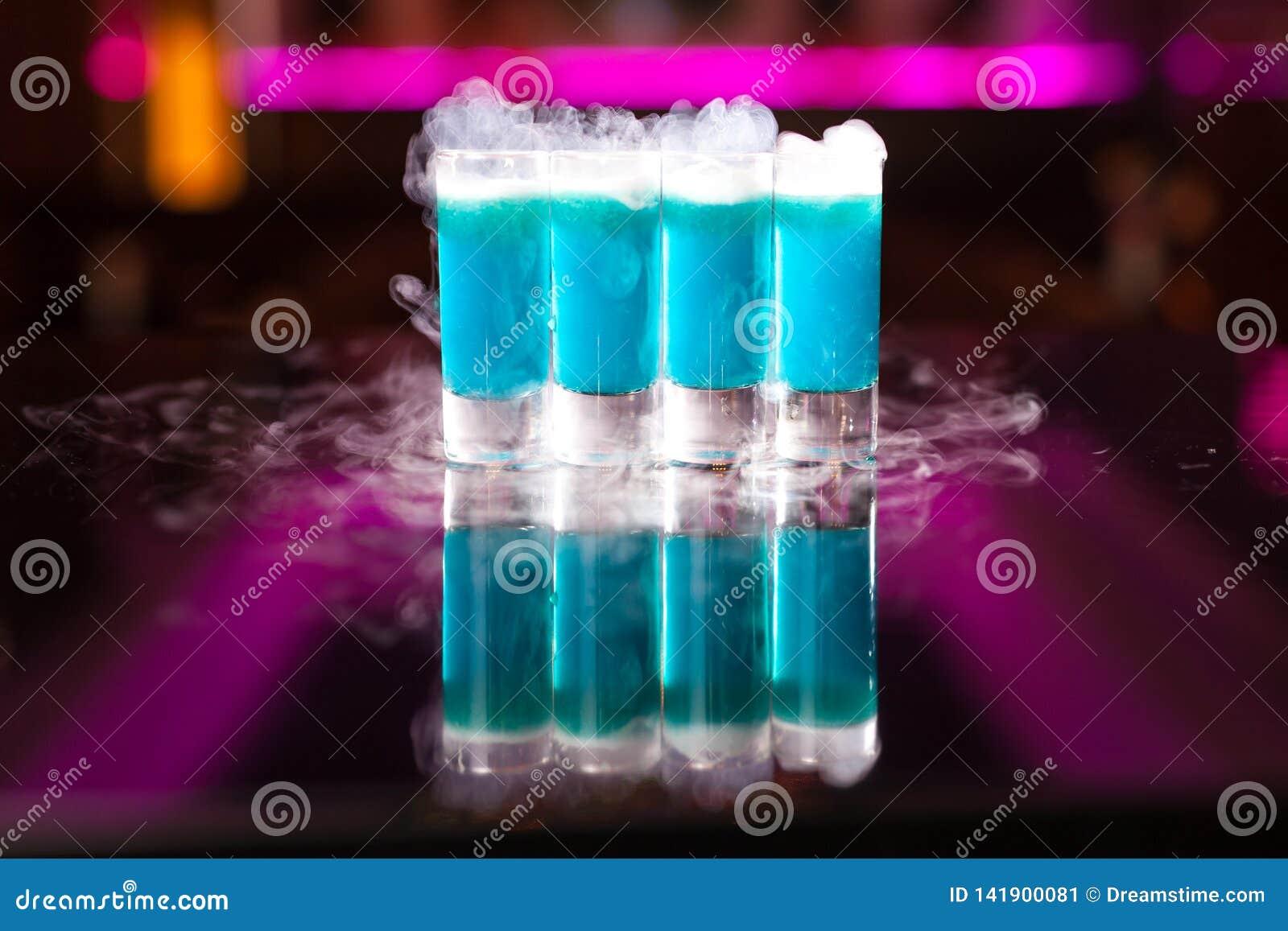 Τέσσερις ανοικτό μπλε πυροβολισμοί κοκτέιλ με τον καπνό στον αντανακλαστικό πίνακα καθρεφτών