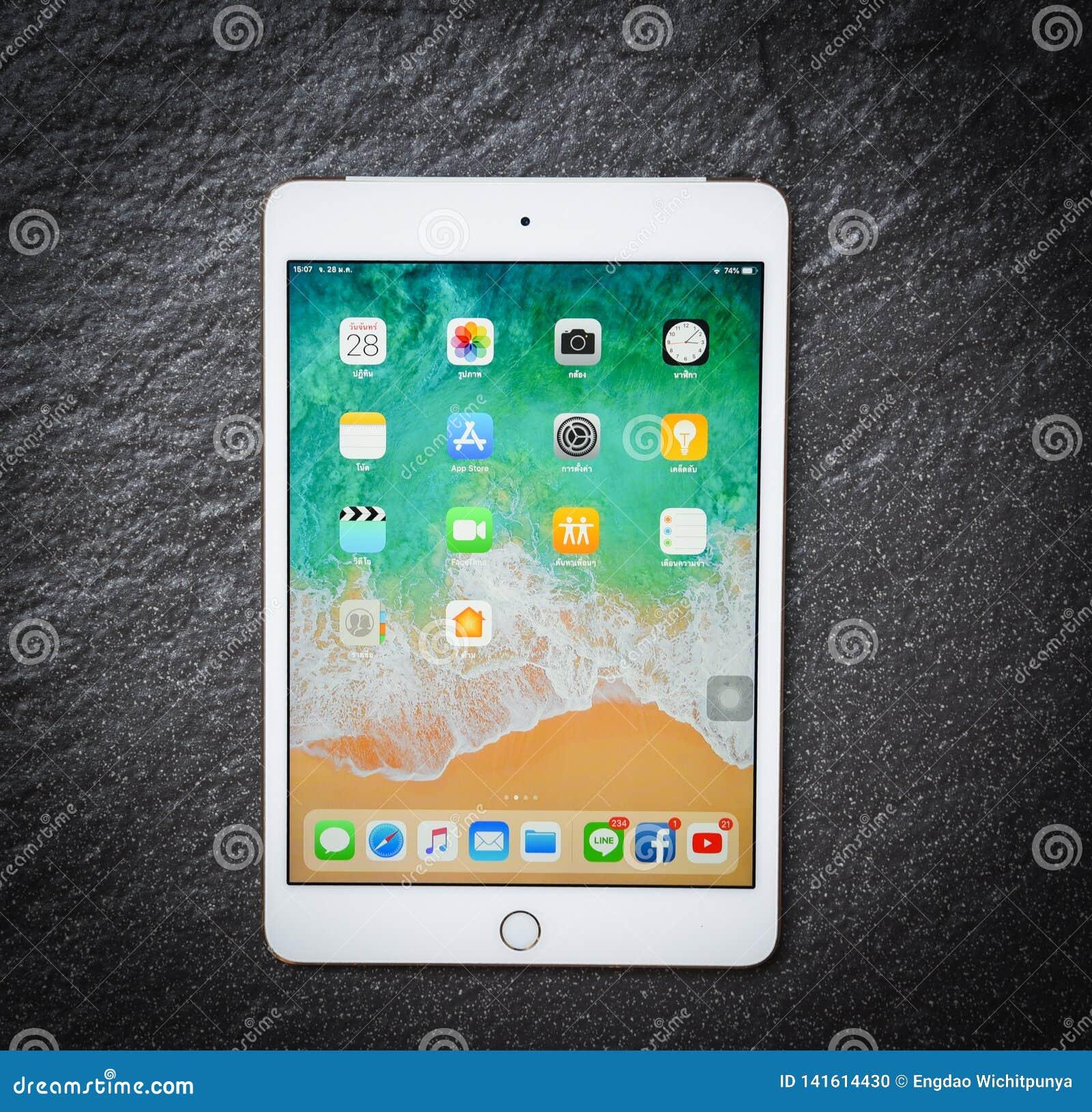 Ταμπλετών μίνι άσπρο χρυσό χρώμα της Apple υπολογιστών νέο iPad με το μέτωπο οθόνης επίδειξης στο σκοτεινό υπόβαθρο
