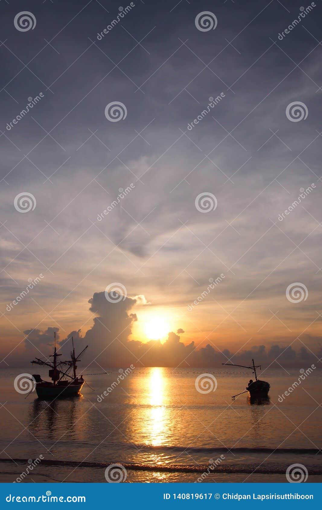Τα αλιευτικά σκάφη με την ανατολή, τα χρώματα του ουρανού πρωινού