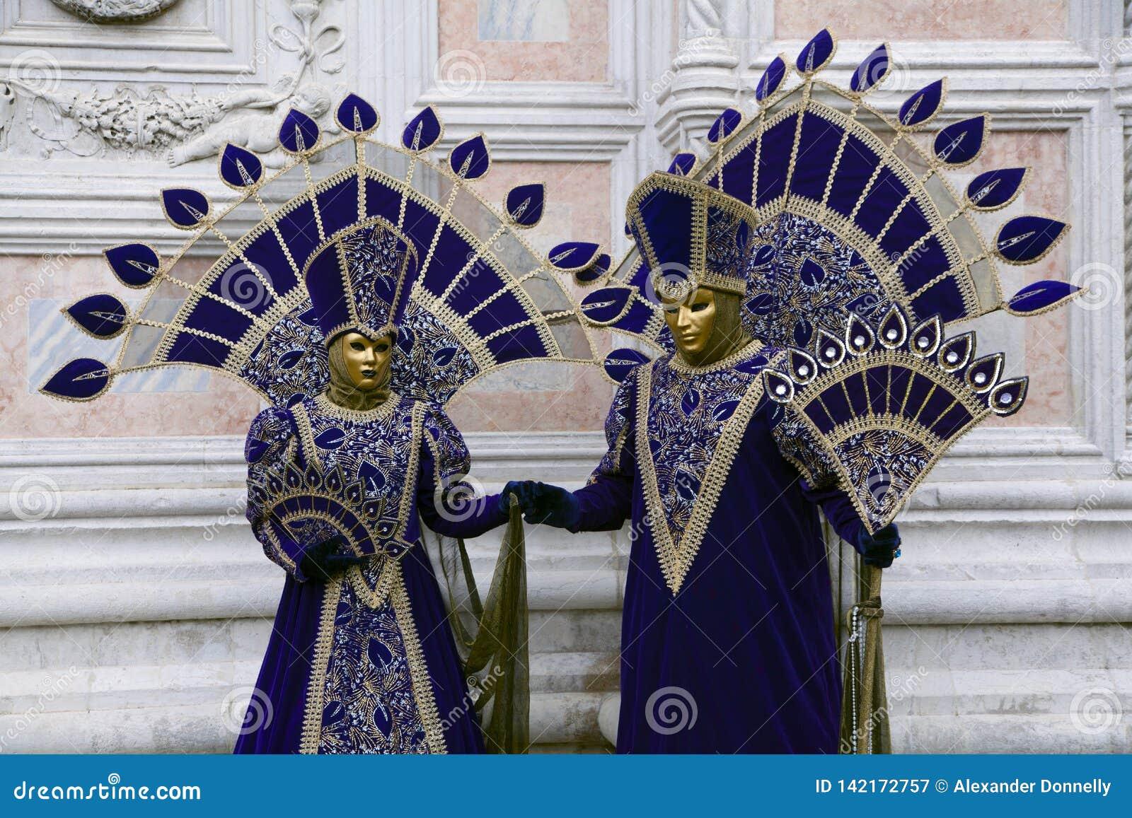 Τα κοστούμια της Βενετίας καρναβάλι σε πορφυρό και το χρυσό και τη Βενετία καλύπτουν το Φεβρουάριο τη Βενετία Ιταλία