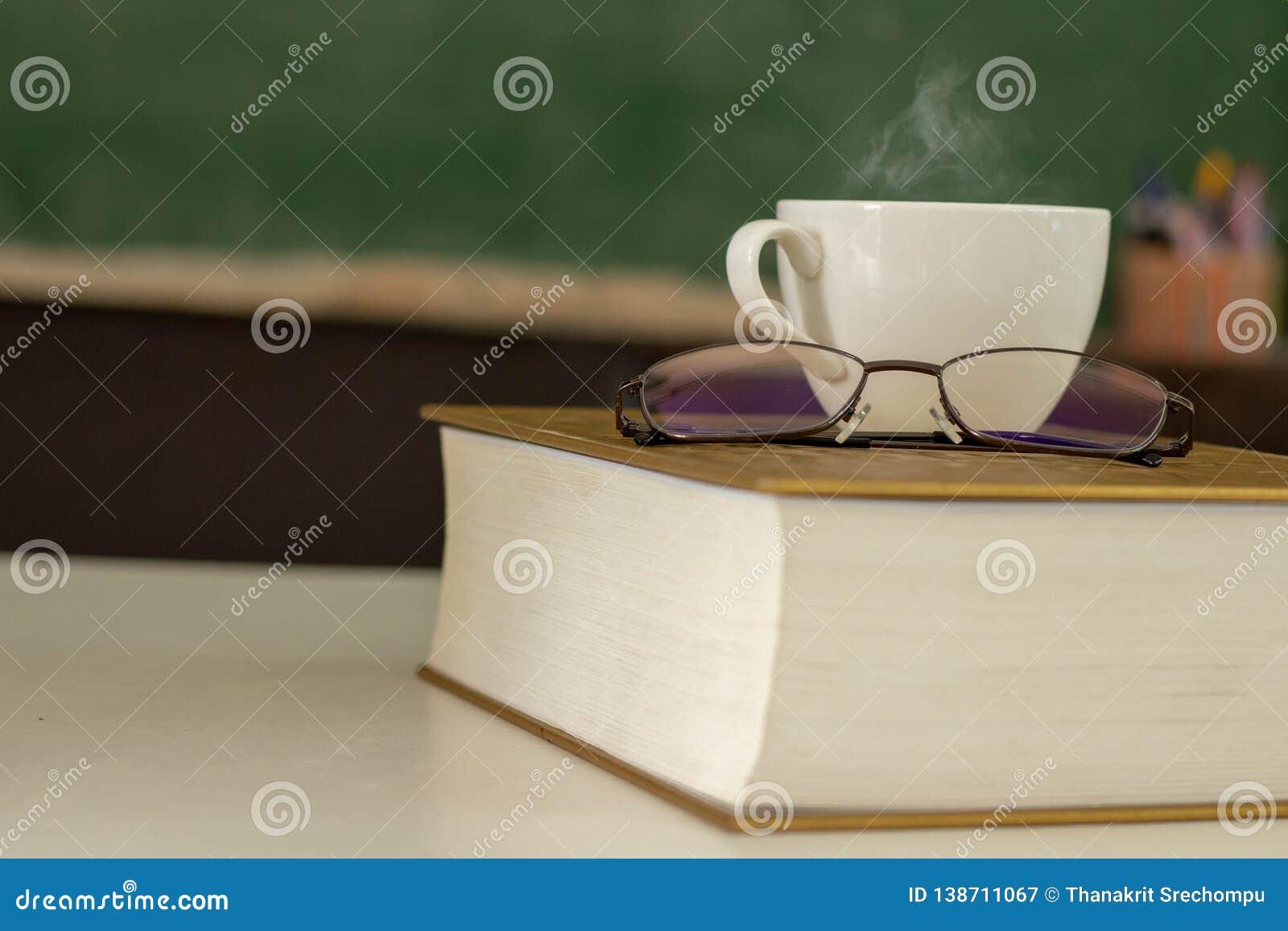 Το άσπρο φλυτζάνι καφέ τοποθετείται στο βιβλίο