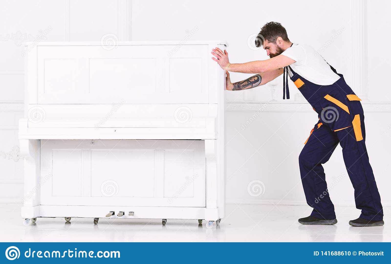 Το άτομο με τη γενειάδα και mustache, εργαζόμενος στις φόρμες ωθεί το πιάνο, το άσπρο υπόβαθρο Ο αγγελιαφόρος παραδίδει τα έπιπλα