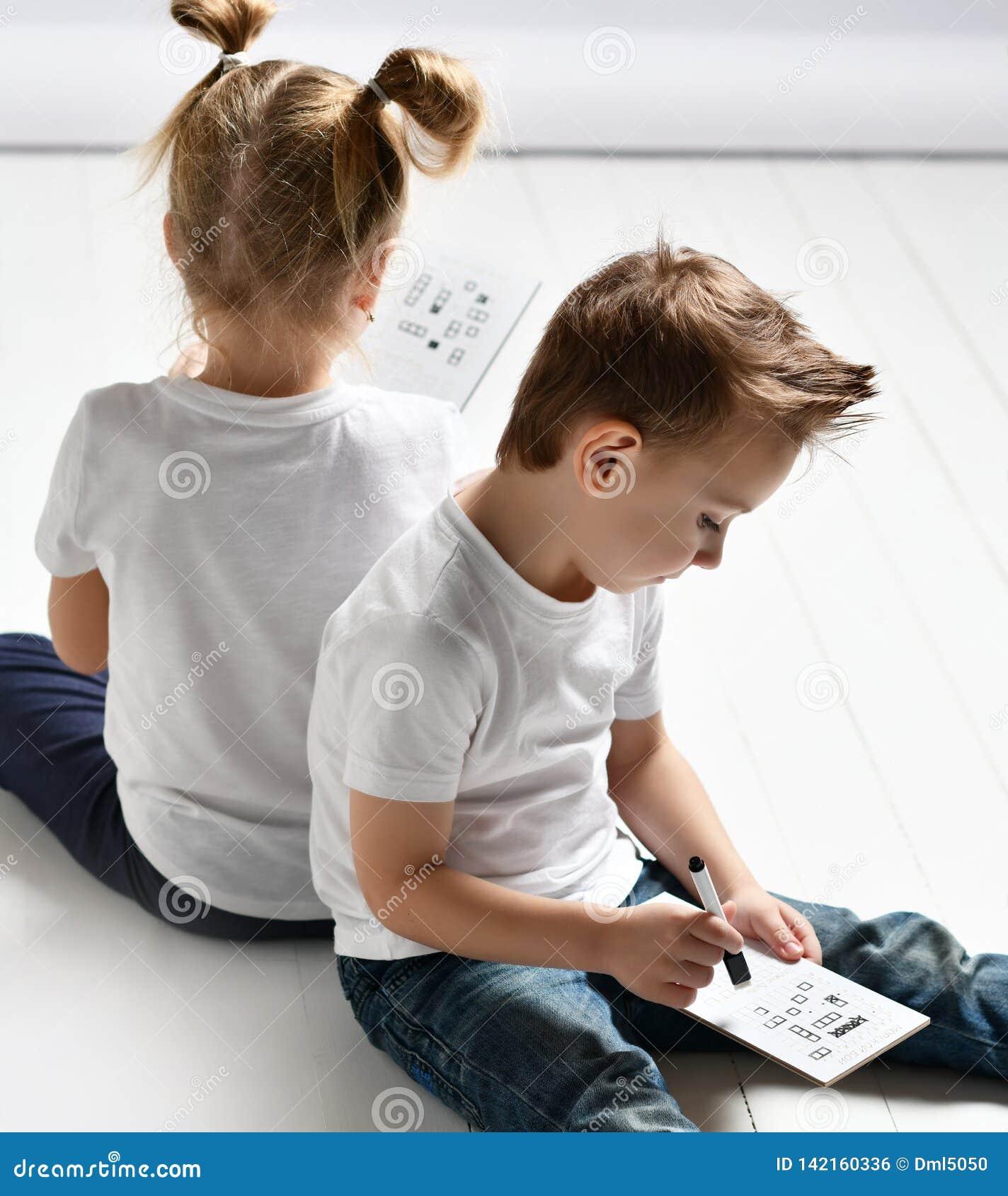 Το αγόρι και το κορίτσι δύο παιδιών στις άσπρα μπλούζες και το τζιν παντελόνι κάθονται το ένα κοντά στο άλλο και παίζουν το θωρηκ