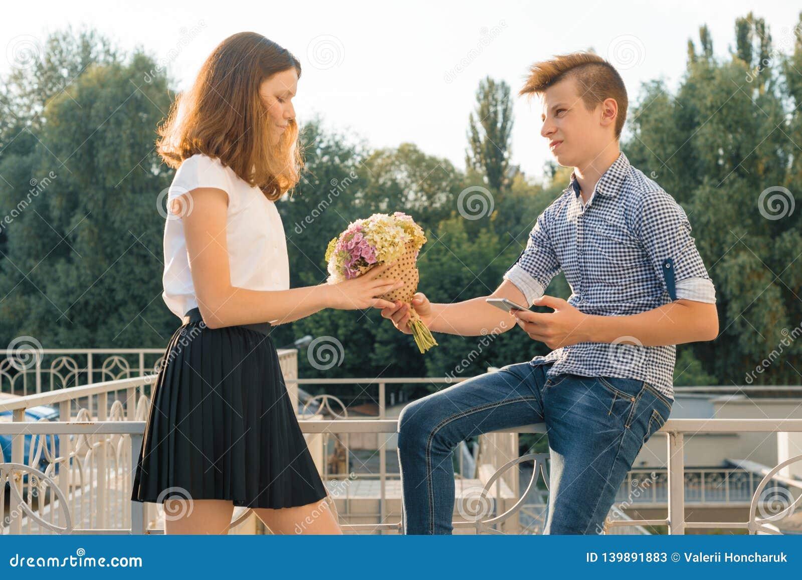 Το αγόρι δίνει την ανθοδέσμη κοριτσιών των λουλουδιών Υπαίθριο πορτρέτο των εφήβων ζευγών, ηλιόλουστη θερινή ημέρα