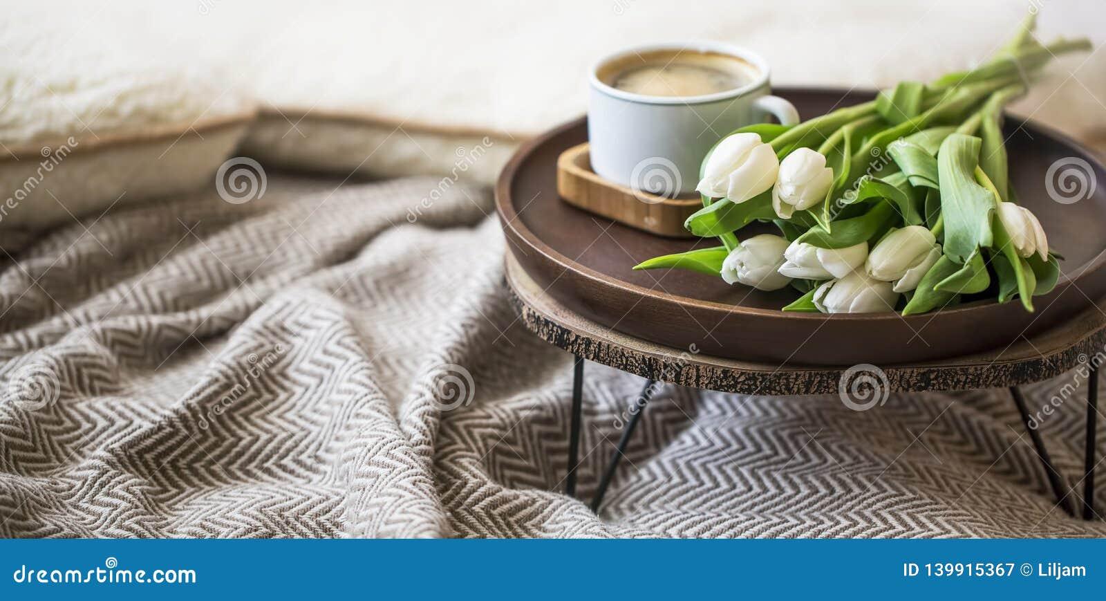 Το εγχώριο εσωτερικό ντεκόρ με τον ξύλινο πίνακα, την ανθοδέσμη λουλουδιών τουλιπών και το φλυτζάνι καφέ, άνετο κάλυμμα, αναπηδά