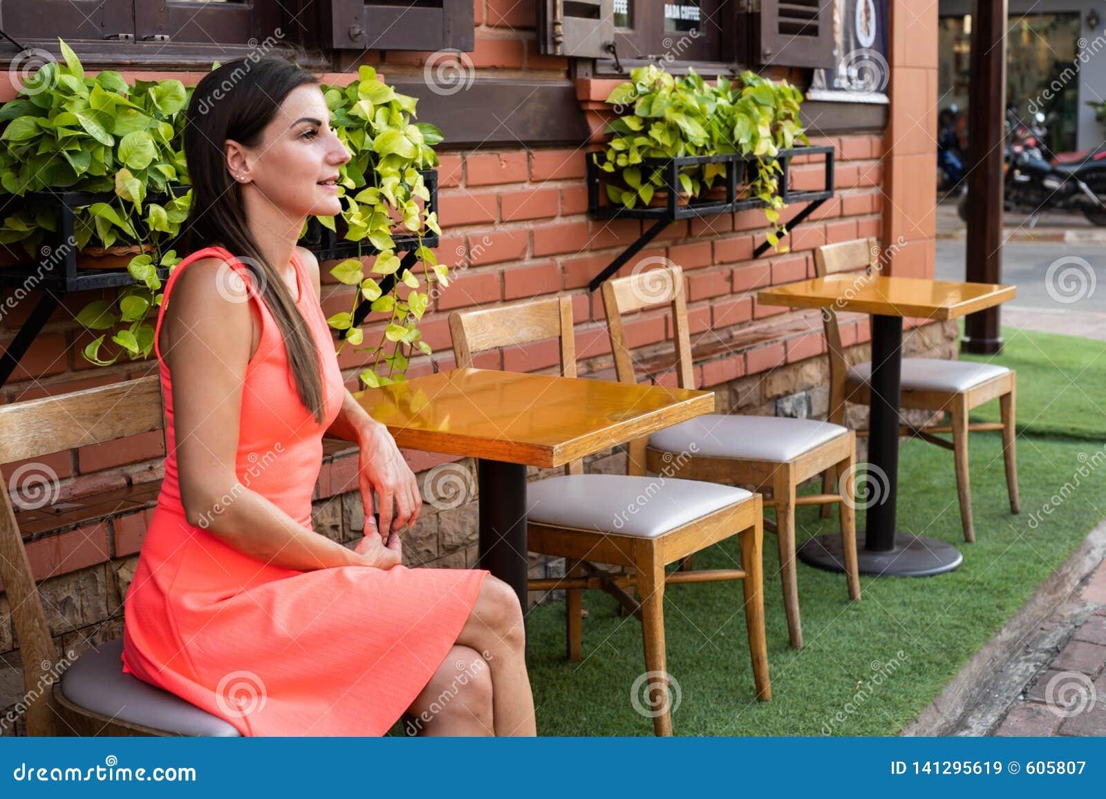 Το θηλυκό περιμένει κάποιο σε έναν καφέ στην οδό της συνεδρίασης, που κυματίζει το χέρι της σε έναν φίλο, 4k