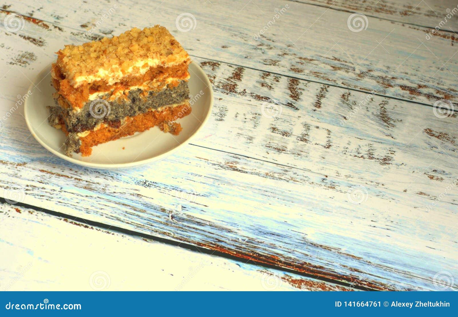 Το κέικ σφουγγαριών με τους σπόρους παπαρουνών σε ένα πιάτο βρίσκεται σε έναν ξύλινο πίνακα