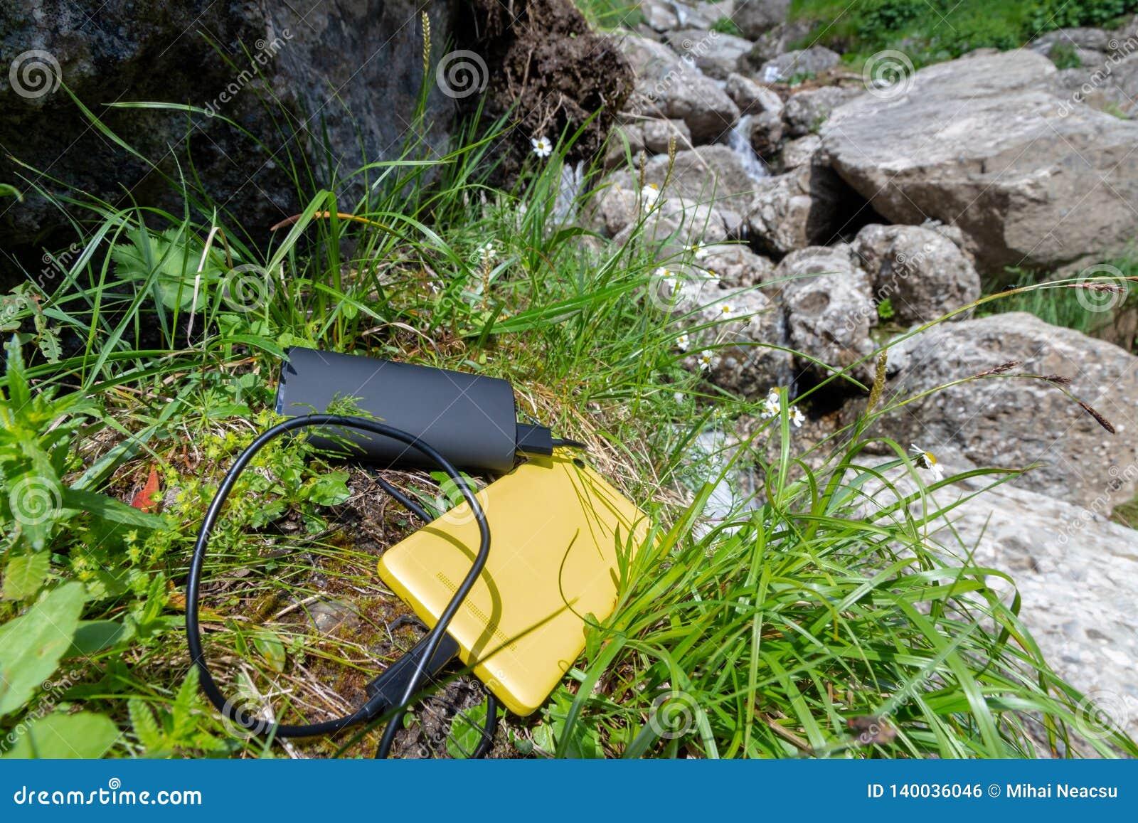 Το κίτρινο smartphone φόρτισε από μια μαύρη εξωτερική μπαταρία powerbank, τοποθετημένος στη χλόη, κοντινοί βράχοι, επάνω στο βουν