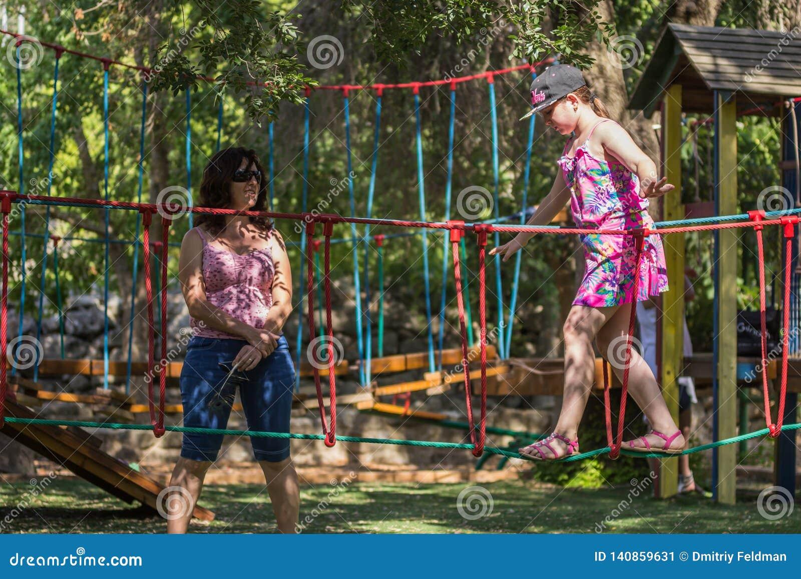 Το κορίτσι συμμετέχει στη γυμναστική στην παιδική χαρά